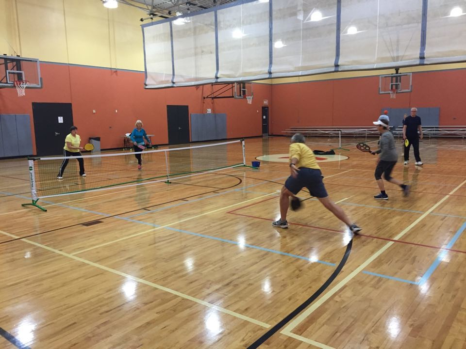 Fletcher Turner, far right, is among the many devoted pickleball players who frequent the Barco-Newton YMCA on Fleming Island. Here, he watches four friends take part in a game of pickleball, which is one of the fastest-growing sports in the U.S.
