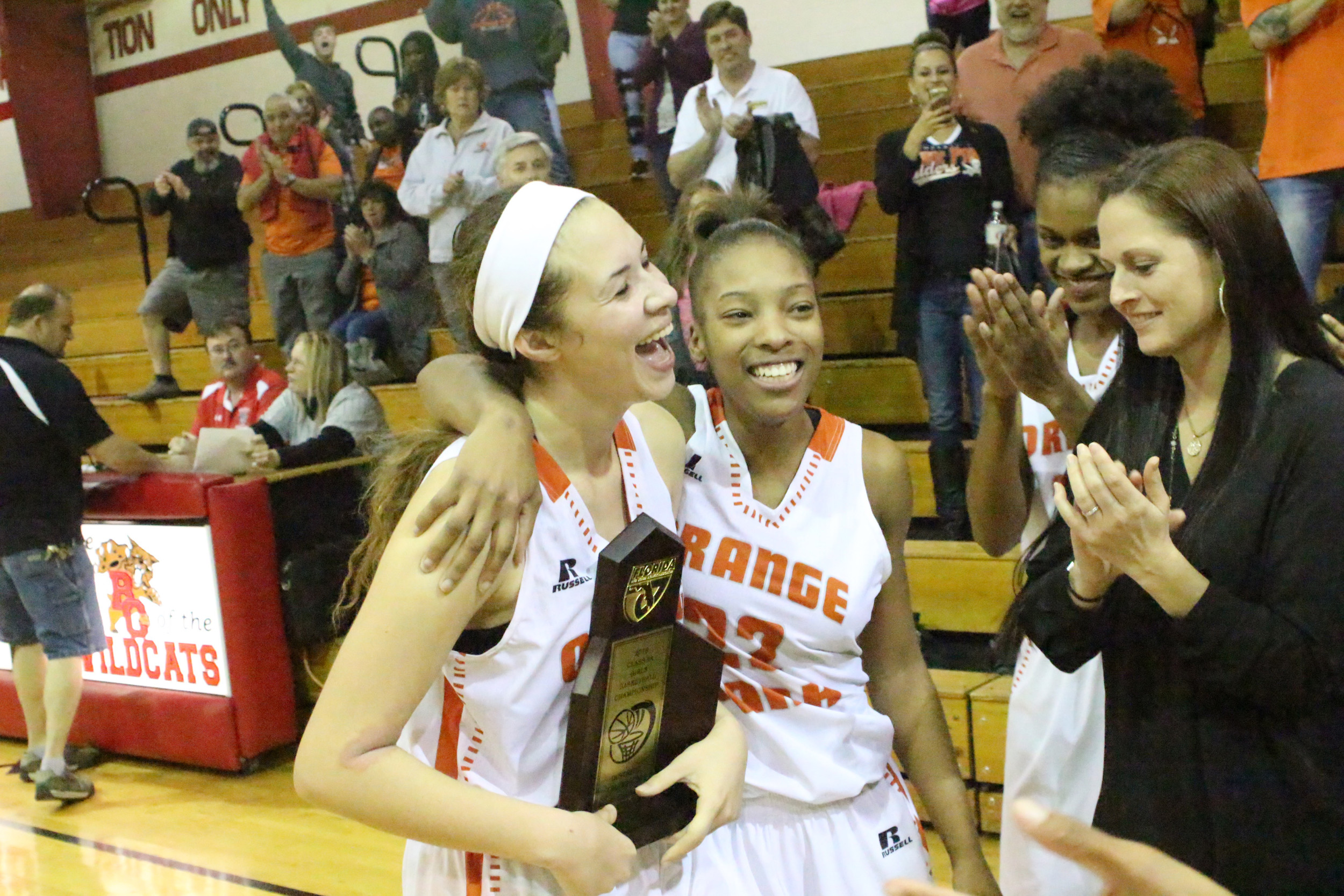 Orange Park High seniors, left to right, Gianni Ruemmeley, Maxine Knox and Shakarri Mack smile with coach Mandi Matricardi after receiving district 4-5A championship trophy after beating Westside High School 51-26 Friday at Baker County High School.