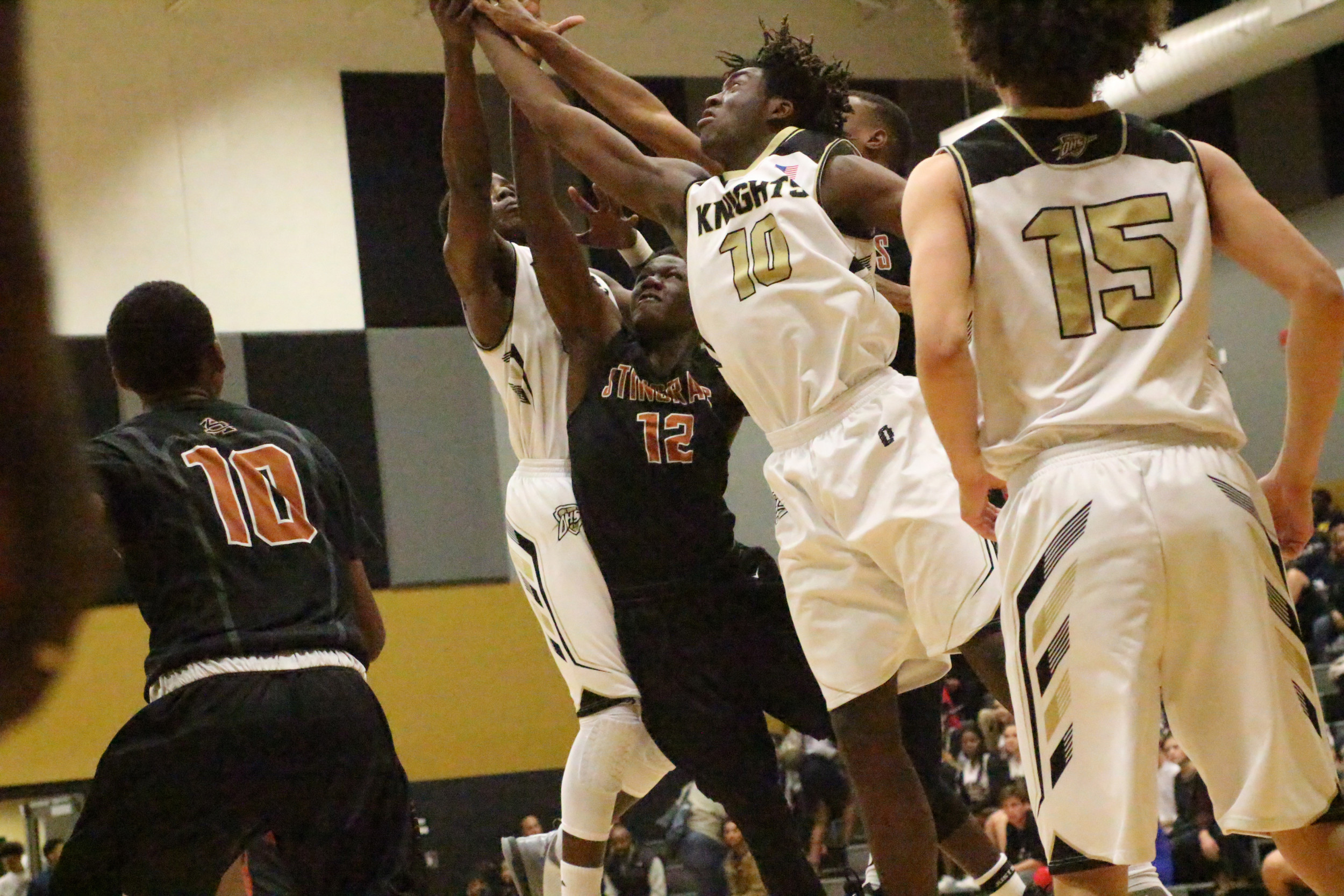 Oakleaf High's Nassir Little stretches for rebound with Jonathan Bryant in first quarter action in Knights overtime region loss to Atlantic Coast High School.