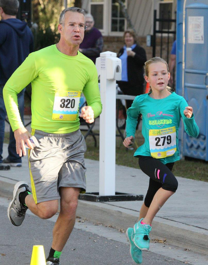 Dad and daughter Joe Knotts, left, and Allie Knotts, 11, stride toward finish line in the River Day 5k run held Saturday at Grace Episcopal Church in Orange Park. Allie Knotts won the Under-11 age group with a time of 28:11.