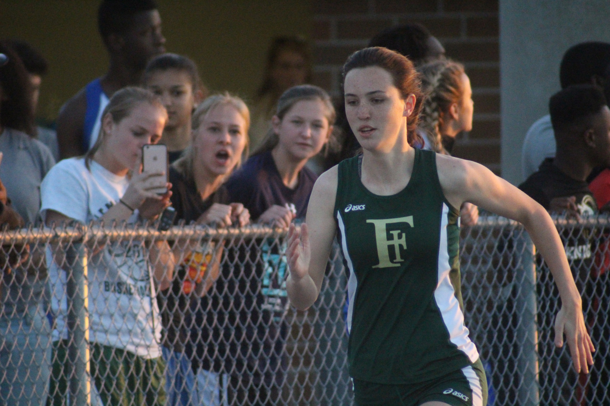 Fleming Island 400 meter runner Aubrey Burke, also a Golden Eagle basketball player, runs by teammates on the fence at the Panther Track Invite.  Burke finished seventh.