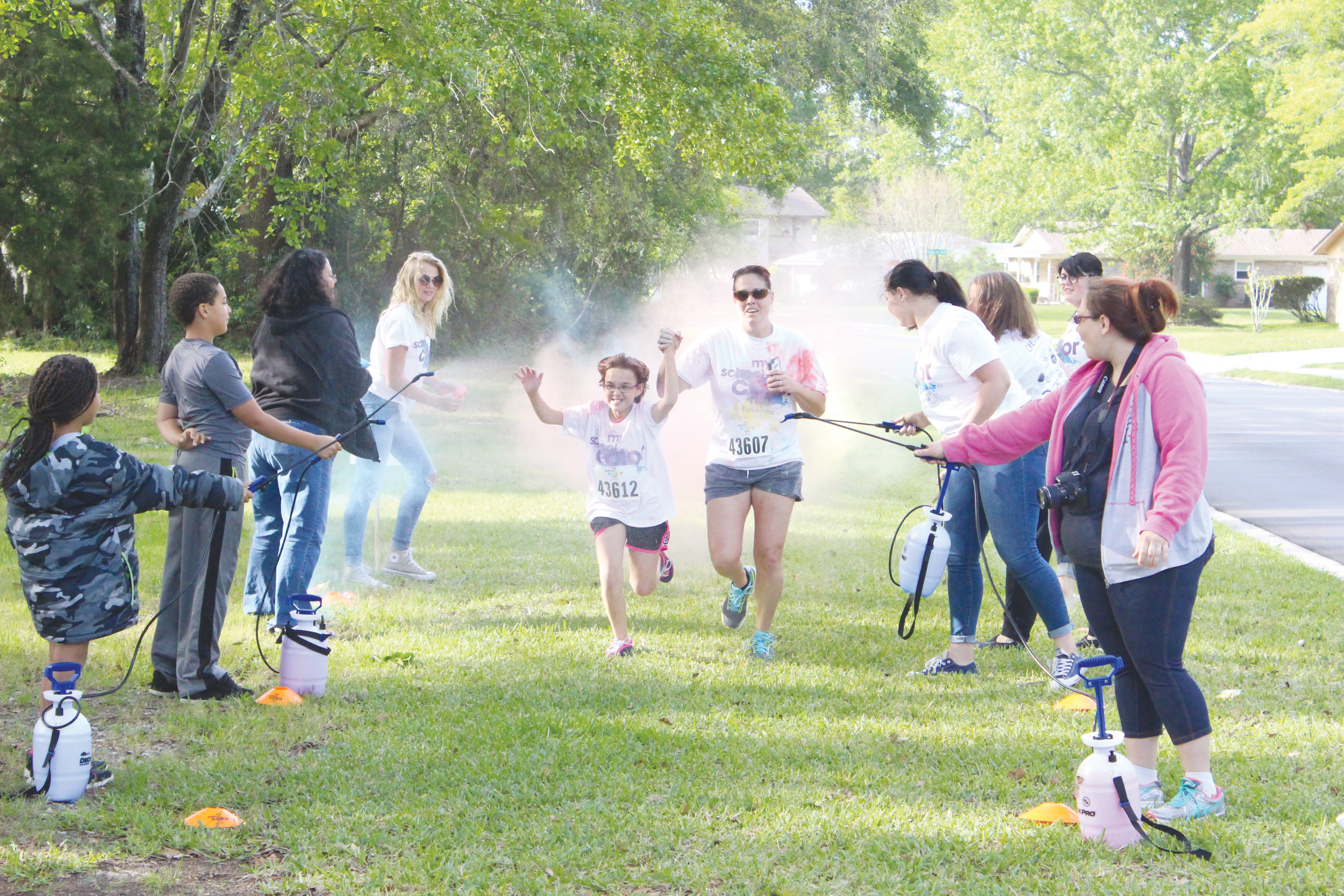 Mother-daughter Roberta and Silvia Tomlinson venture through cloud of color and spray at finish of Color Me Rad 5K staged at the OPPAA campus on Saturday.