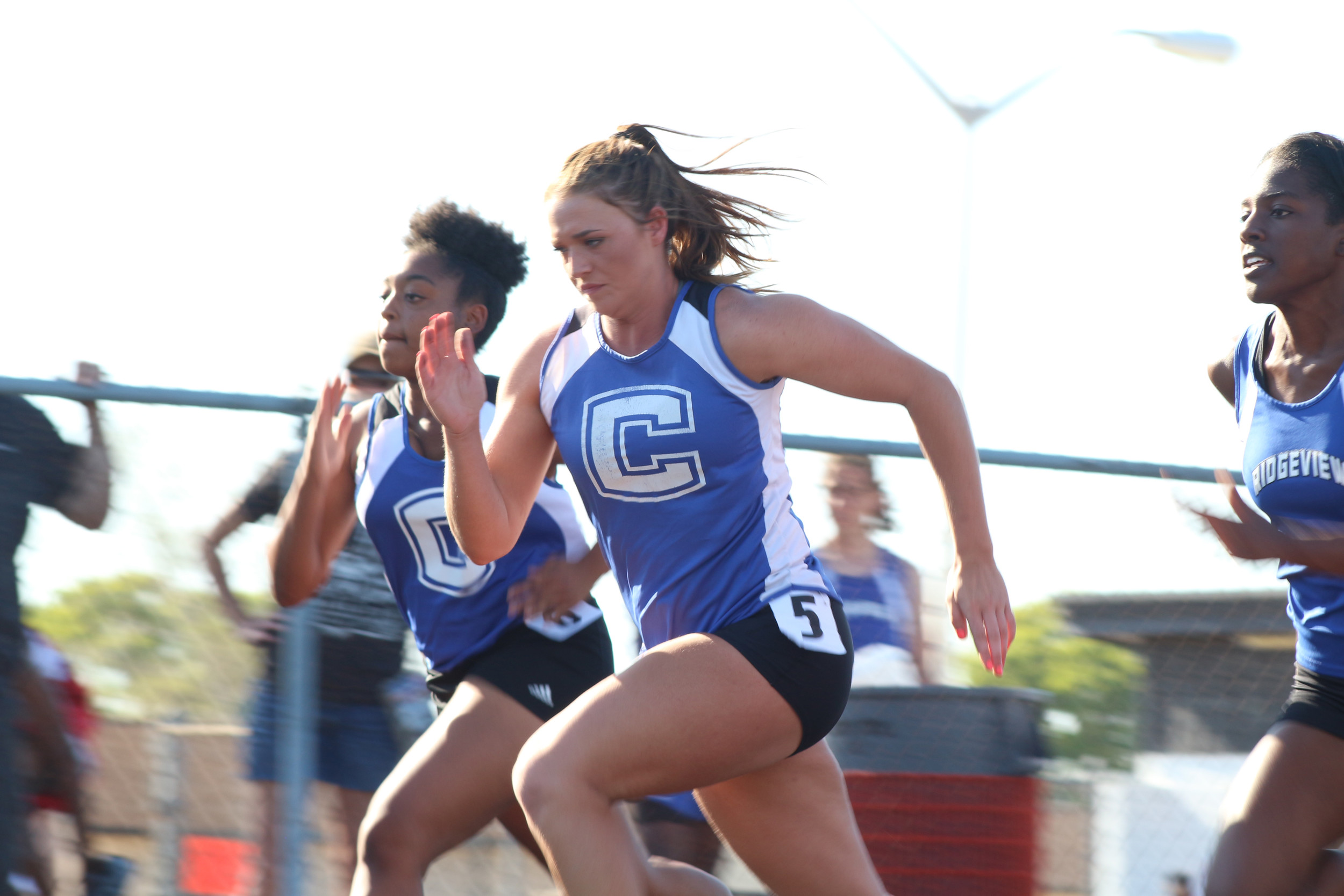 Top: Clay High sprinter Christy Carlisle blasts from start of 100 meter dash.