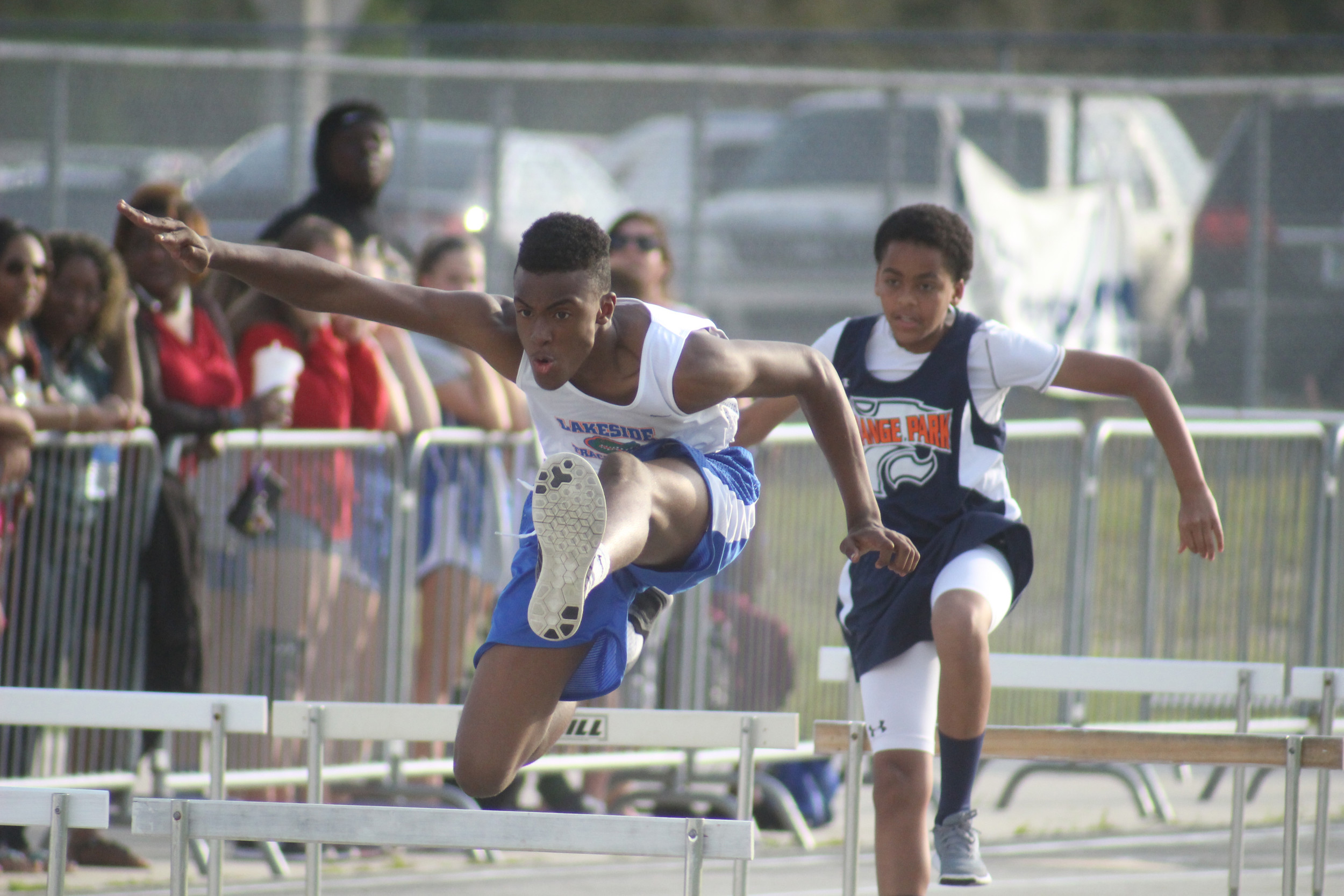 Lakeside Junior High hurdler Albert Williams, here battling with Orange Park Junior High in recent dual match, will be striding out in the Clay County Junior High Track and Field Championships to be held Fri., April 15 at Orange Park High School.