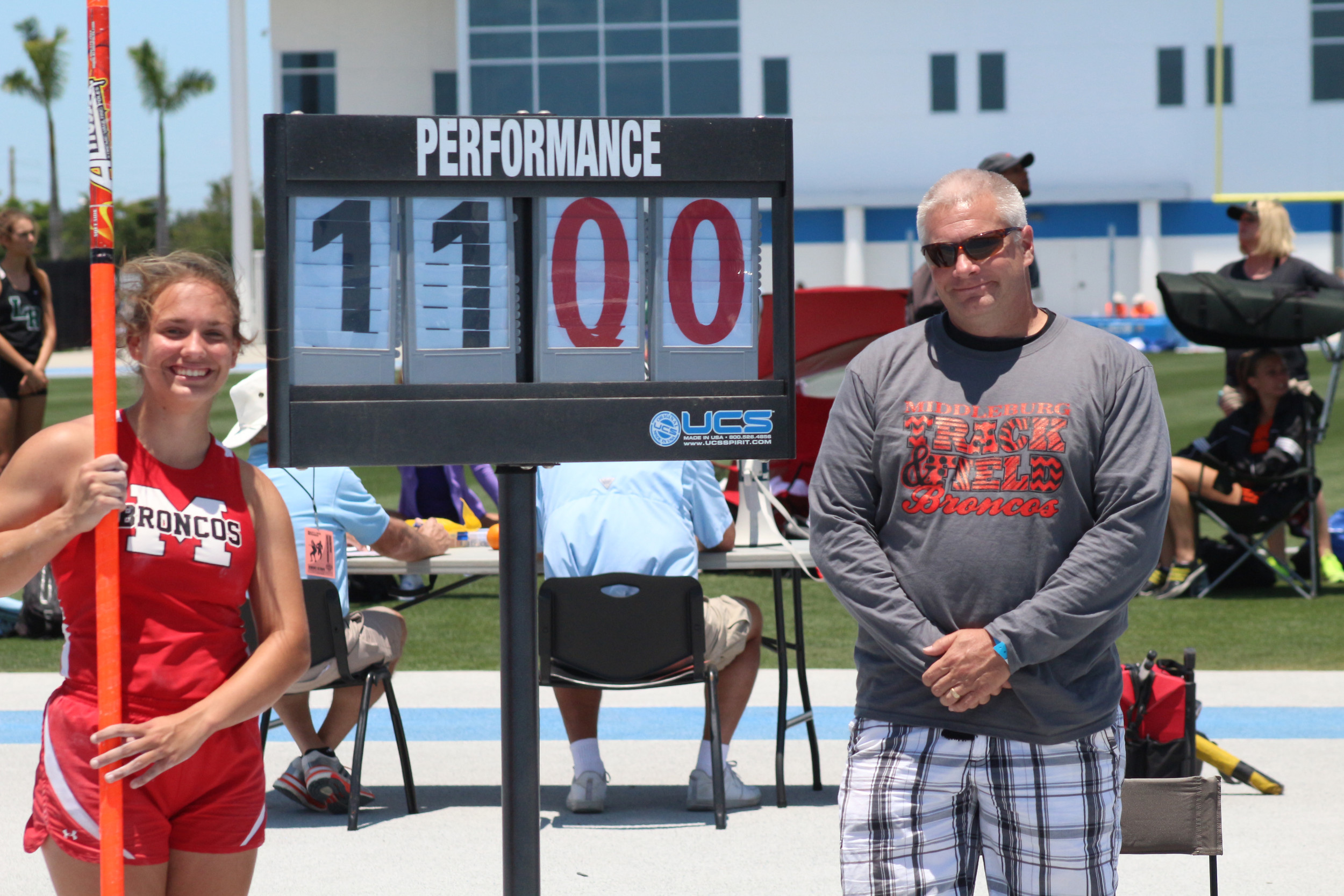 Class 3A girls pole vault champion Samantha Stelmaszek, left, smiles with Middleburg High track coach Craig Martin after she captured Middleburg's first-ever gold medal on Friday.