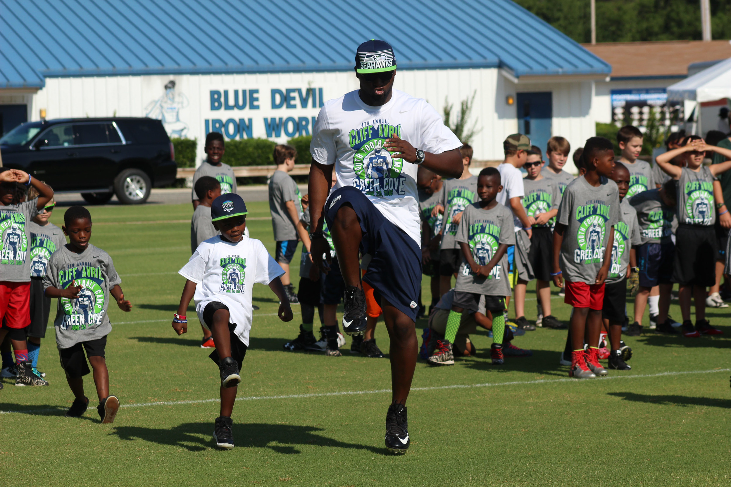 Former Blue Devil Cliff Avril does some high-stepping in warmup drills at the Cliff Avril Youth Football Camp held Saturday at Clay High School.