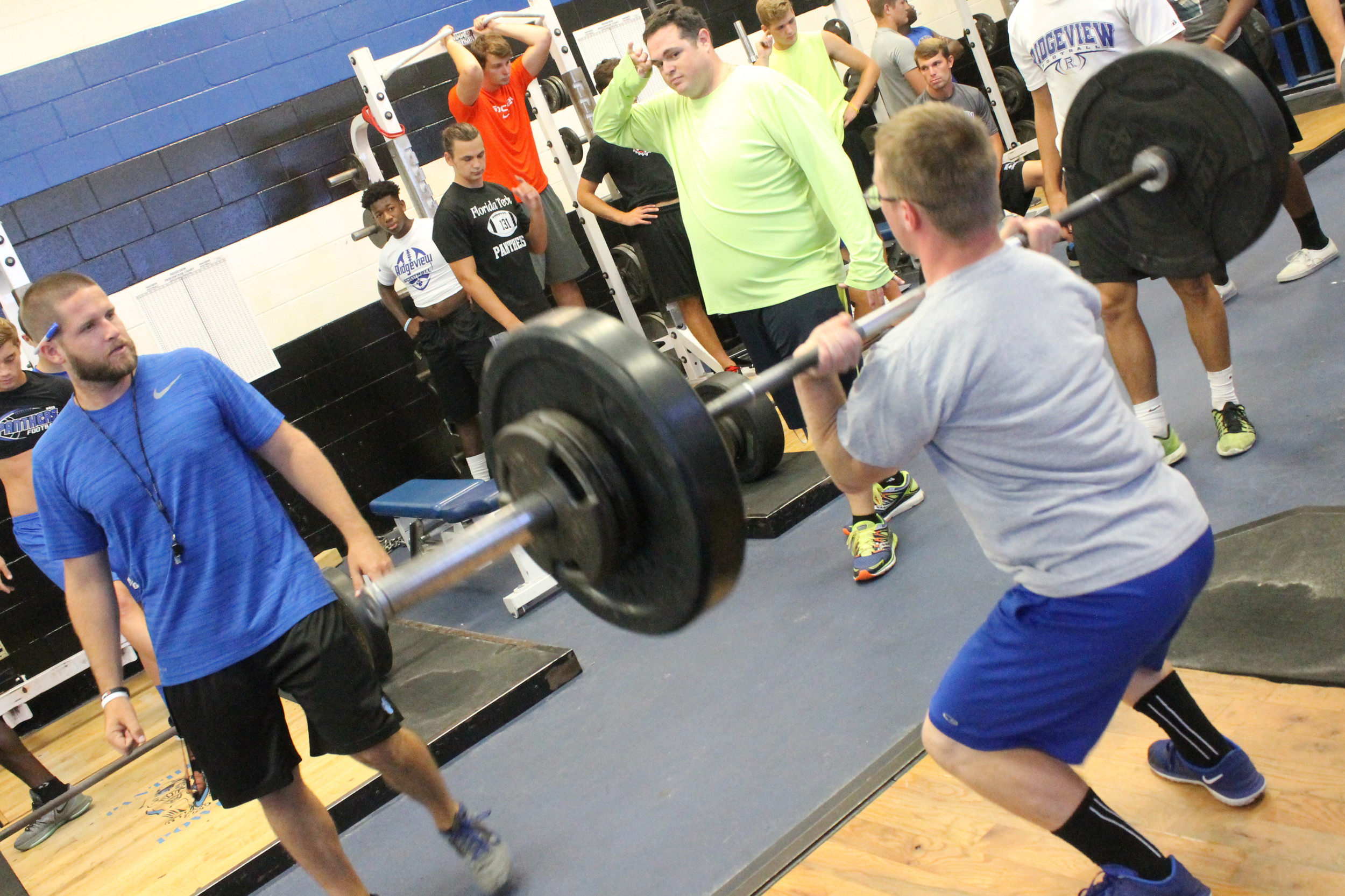Ridgeview High first year coach Cameron Porch, left, watches fullback Nick Freeze press up some weights. Porch, also a weightlift coach, has pushed his Panthers in the weight room with enthusiastic improvements over the summer.