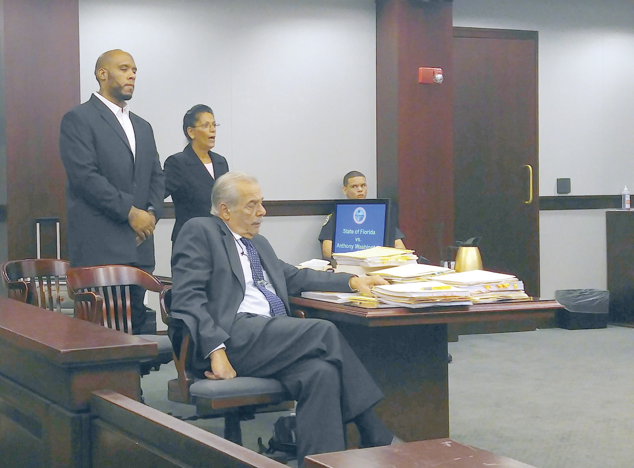 Defendant Anthony Washington (left) stands in court alongside his attorneys, Janis Warren and Tom Fallis.