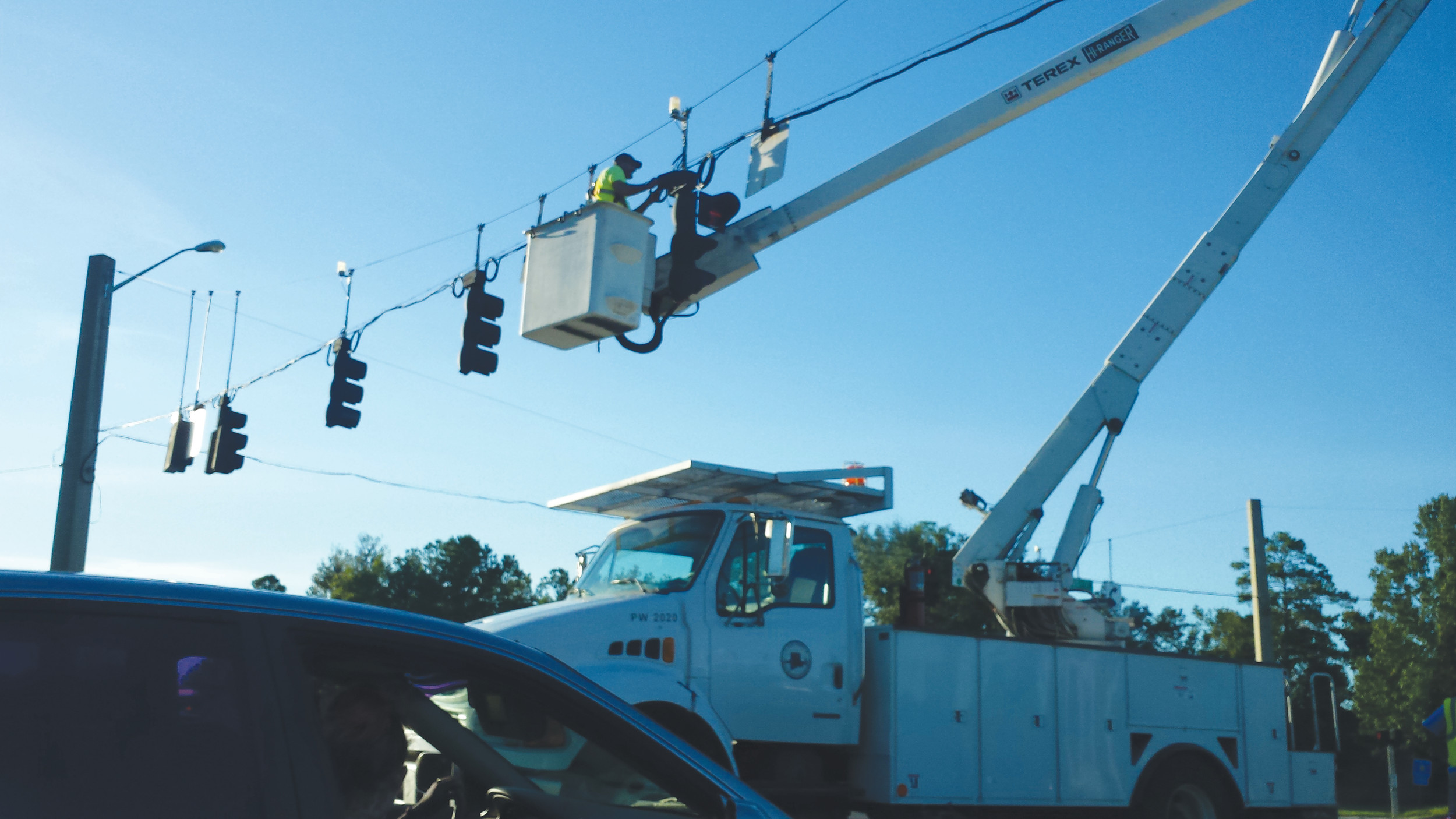 Clay County work crews dangle over the intersection of U.S. 17 and County Road 220 to repair the traffic light in the wake of Hurricane Matthew.