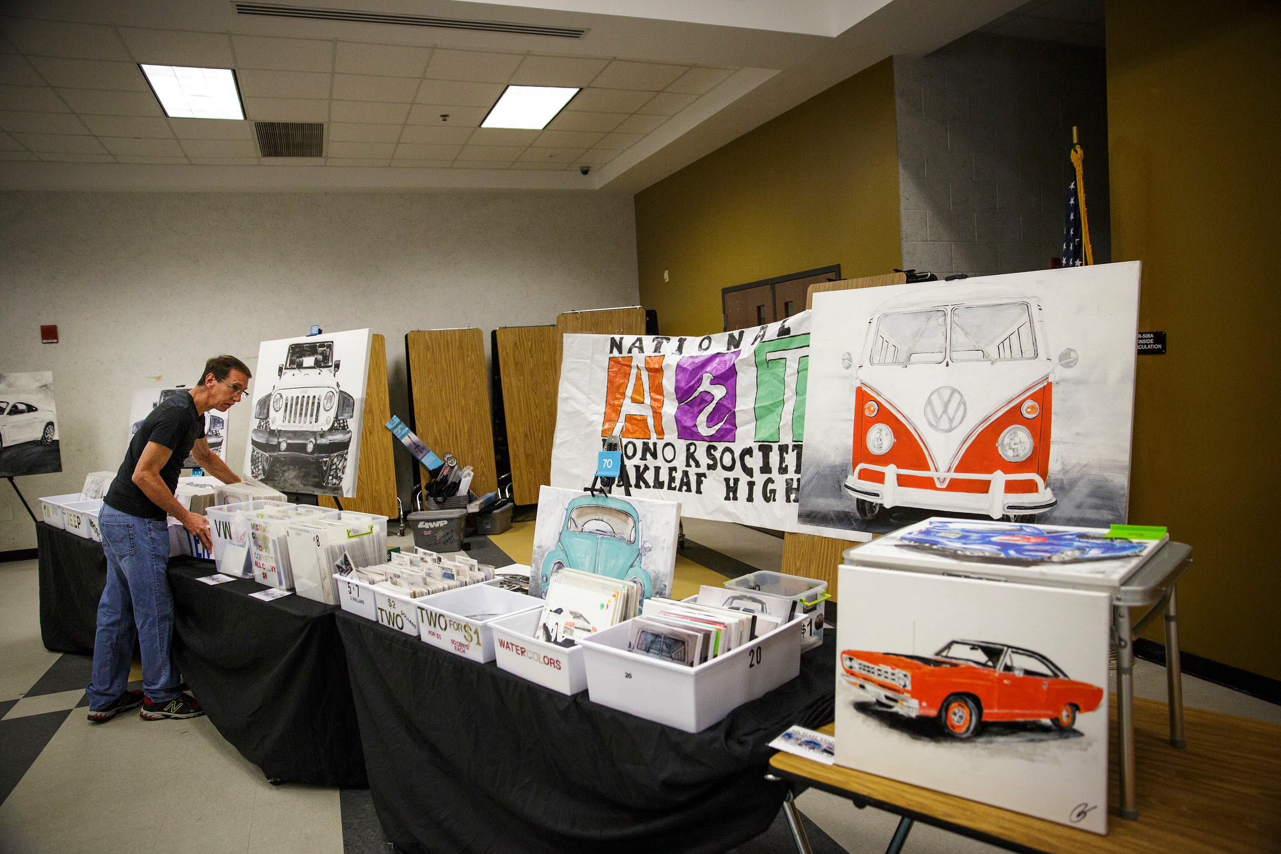 Local artist Michael Viafora organizes prints at his booth at Oakleaf High School during the school's annual Art Walk event.