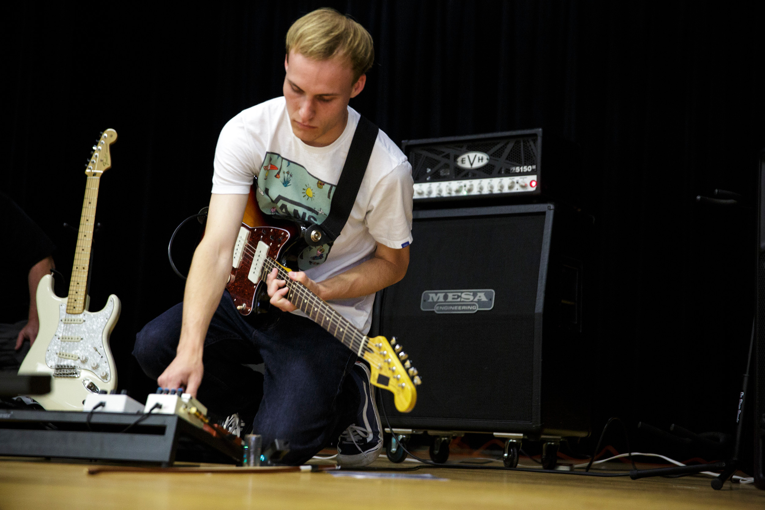 "Oakleaf High School student Jonathan Richardson adjusts knobs on an effect pedal during a guitar performance called ""This Earth is Ours."""