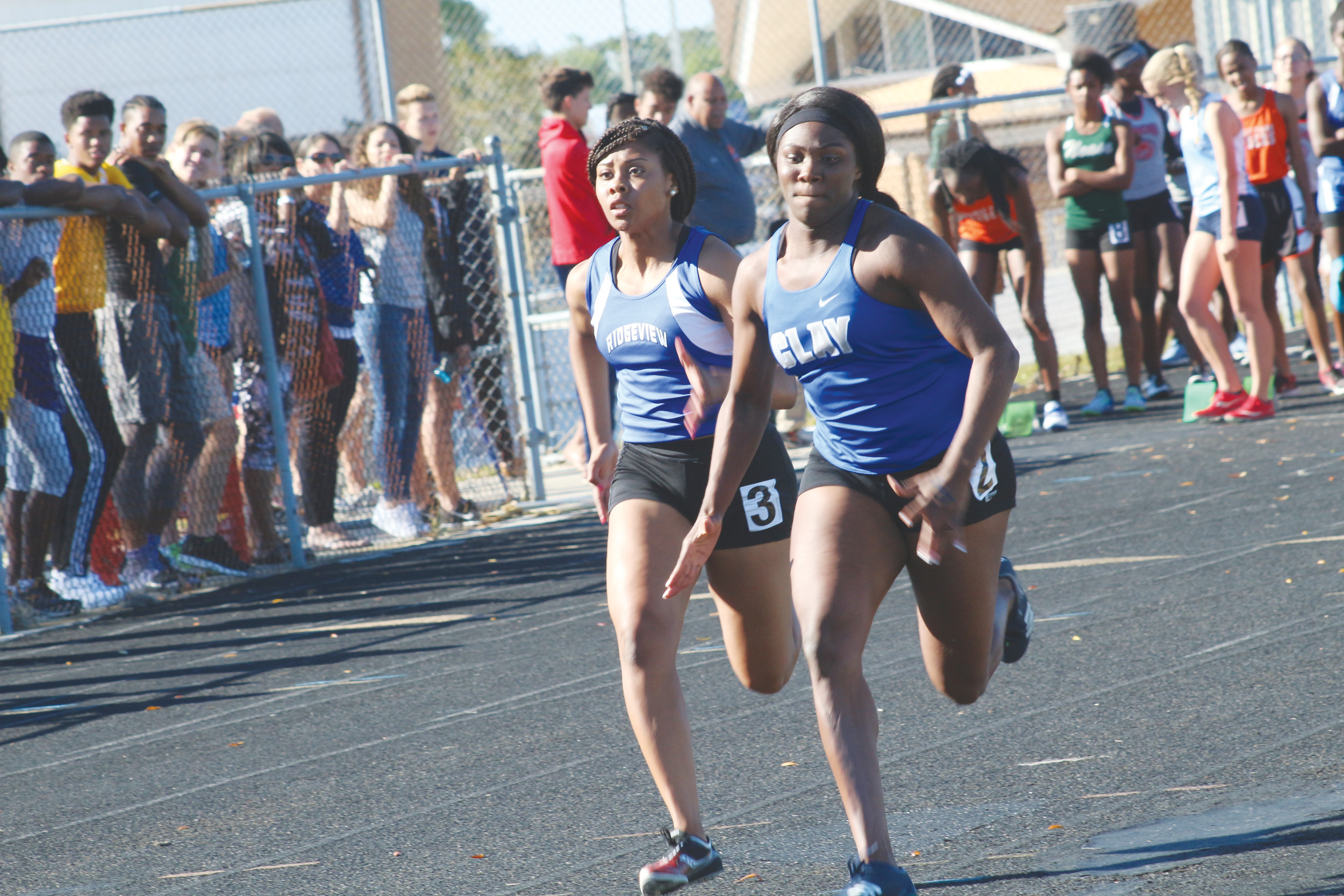 Clay High sprinter Erykah Murray, right, battles with Ridgeview's Chereese McEwan in Don Hall 100 meters. Murray finished in top four for district 3-2A 100 and 200 meter dashes to advance to the region 1-2A championships to be held April 25 at Bolles.