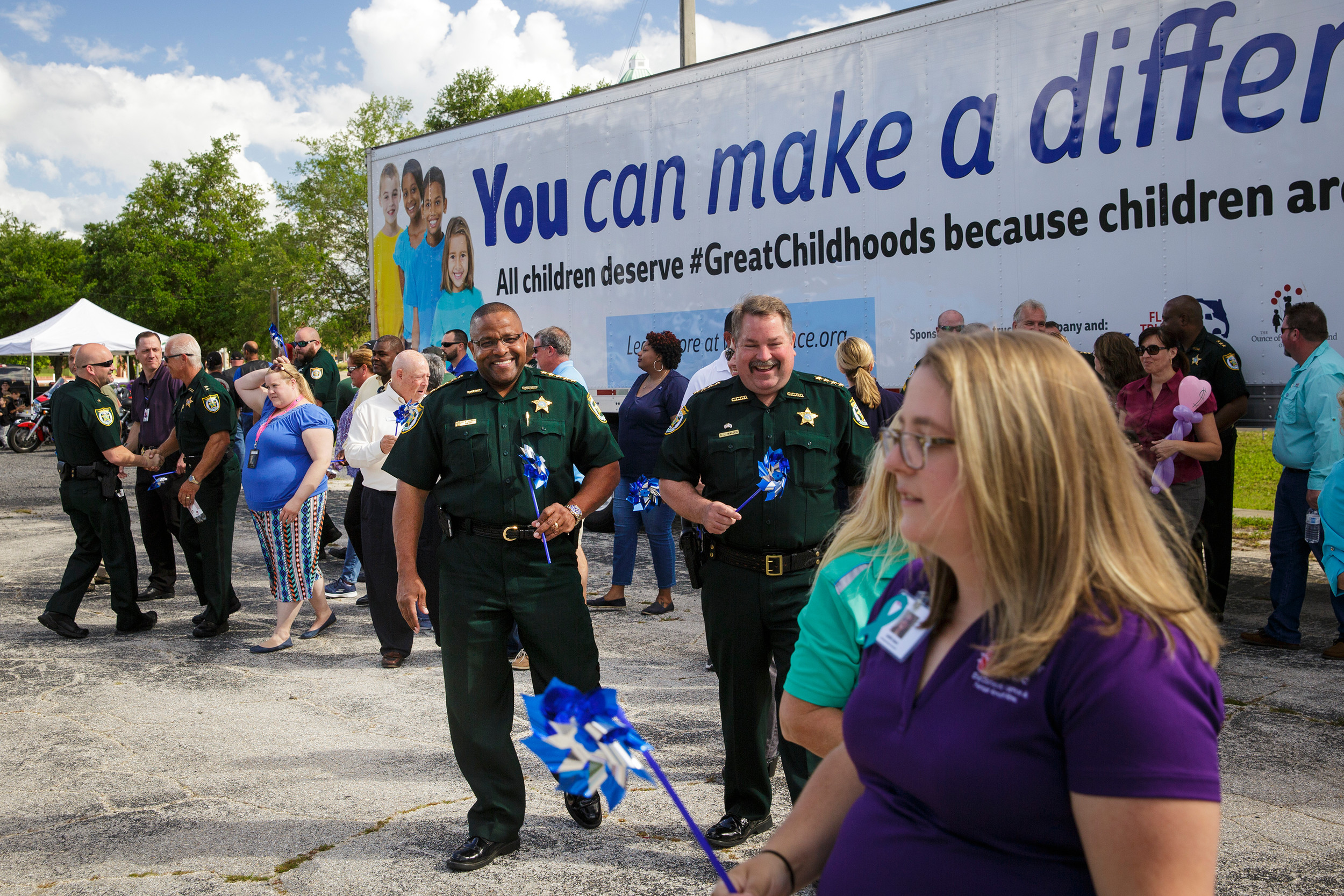 Clay County Sheriff Daryl Daniels, center, walks with a blue pinwheel after participating in a group photo at Green Cove Springs' Child Abuse Awareness Day held in conjunction with national Child Abuse Prevention month.