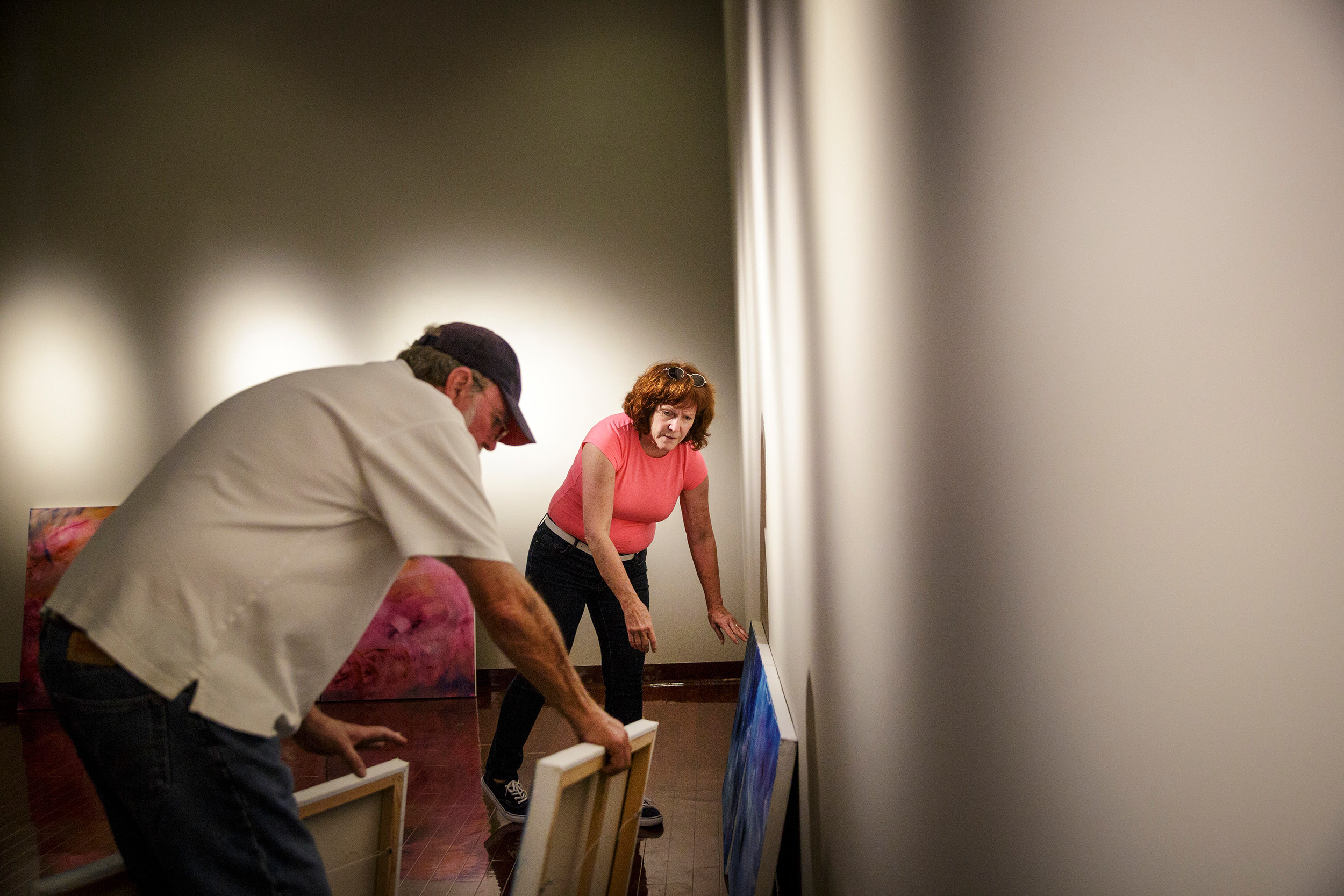 "Artist Margaret Schnebly Hodge, right, installs her series ""Dark Matter, Dark Energy"" with her husband Larry Hodge at the Thrasher-Horne Center for the Arts at St. Johns River State College."