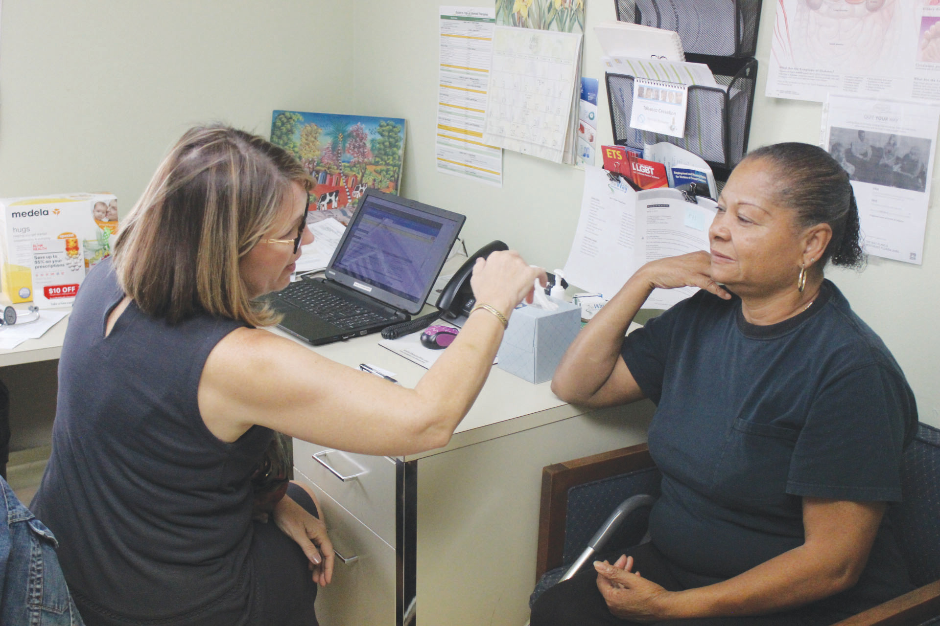 Nurse Practitioner Sandra Schellhorn checks out patient Juanita Johnson in one of the clinic's exam rooms.