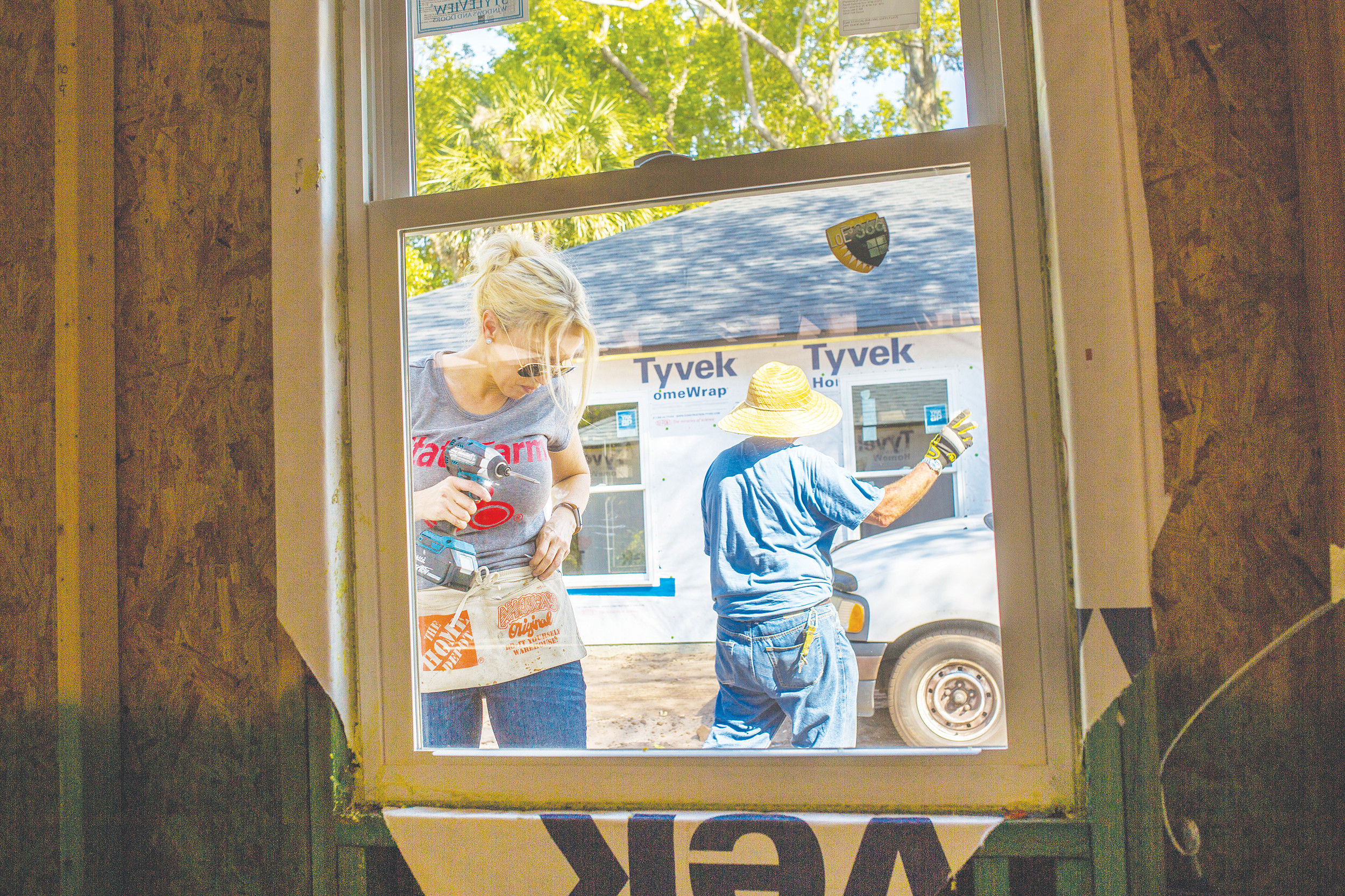 State Farm's Katherine Baustert works to secure a window in a house being built by the Clay County Habitat for Humanity Thursday in Green Cove Springs.
