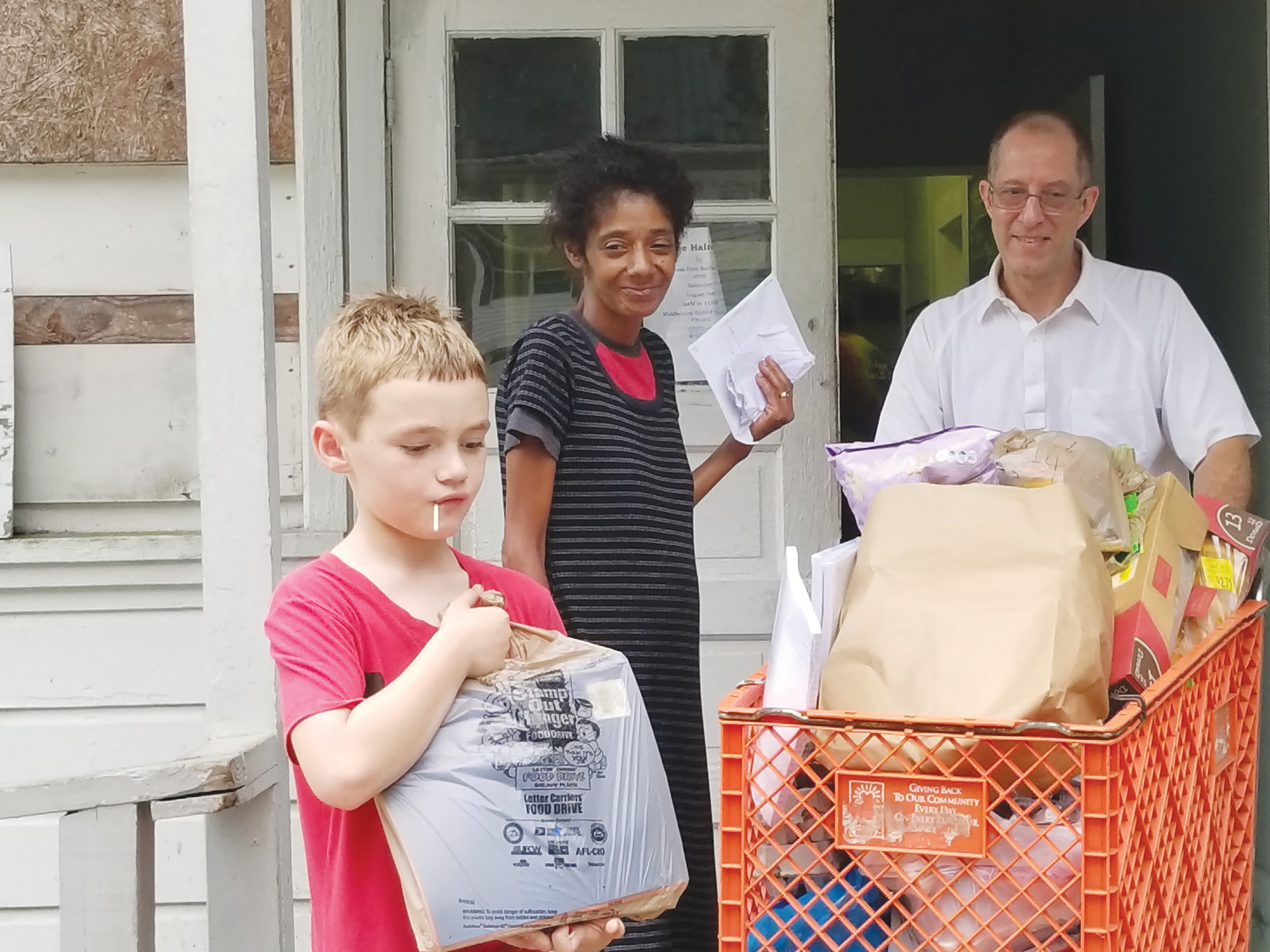 Margaret Hines, center, and her son Carlton, left are grateful for the Aug. 3 school supply distribution at Middleburg Methodist Church where volunteer Ray Ashcraft pushes the cart of food and school supplies outside.