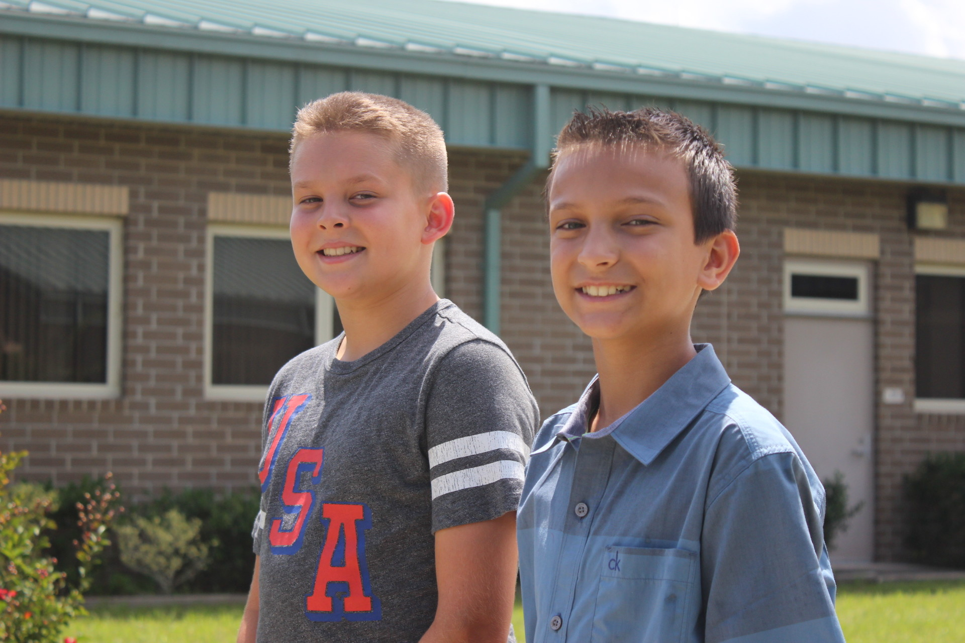 From left, Nate Helmuth and Isaac Davis, both 11, stand at the same pole they folded the United States flag at during an Aug. 17 rainstorm at Coppergate Elementary.