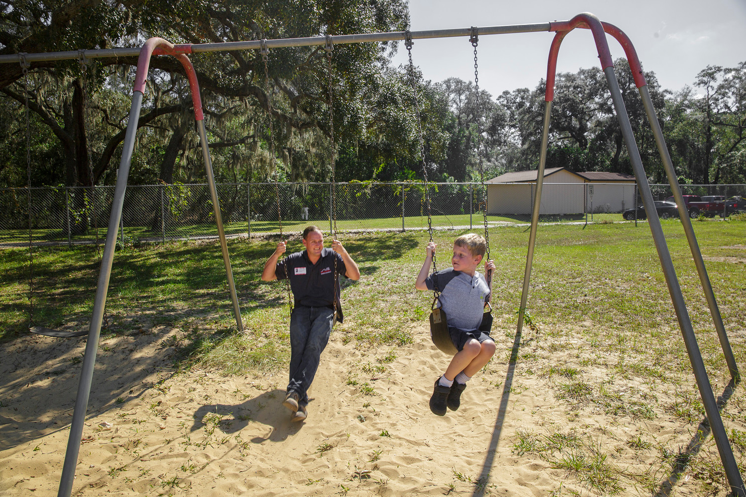 Jake Boyles, left, and his son Jacob see who can swing higher last week at Middleburg Elementary when dads were encouraged to come spend lunch with their students as part of a national campaign.