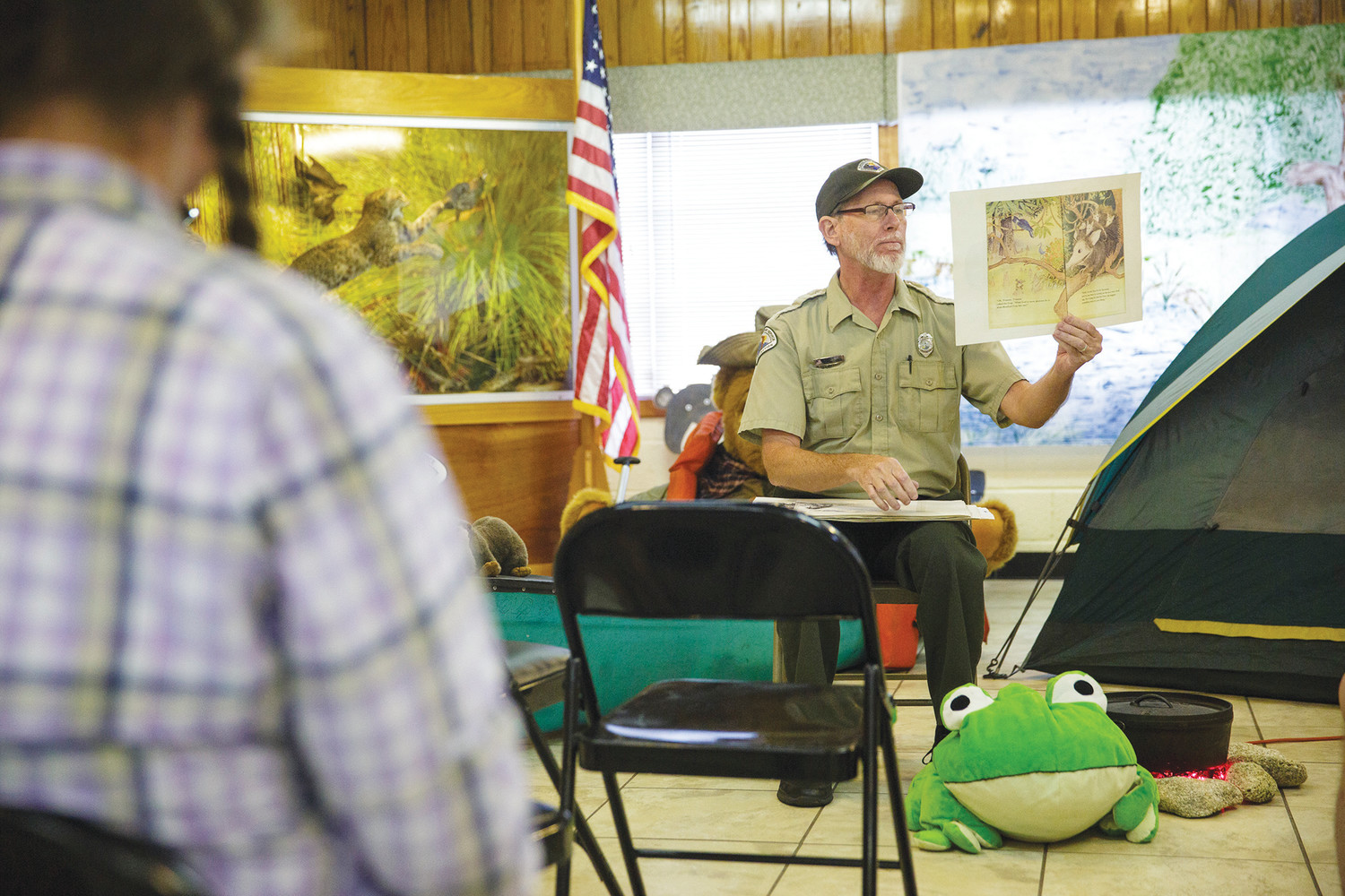 "Gold Head Branch State Park Ranger Steve Earl reads the book ""The Wide-Mouthed Frog"" to a group of children Saturday at the park during their annual Read with the Trees event in partnership with the Melrose Public Library."