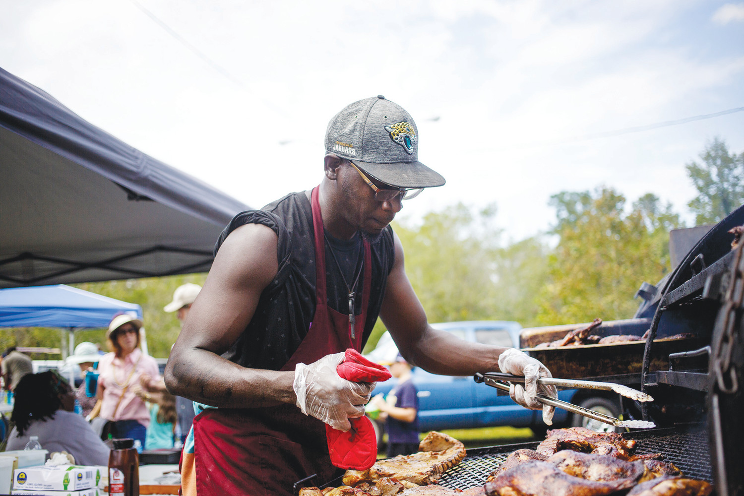 Jacksonville restauranteur Isaac Hall works the smoker Saturday at the Soul Food Festival in Green Cove Springs. Hall's aromatic meats drew patrons throughout the day who came to his tent, Good Food 247, seeking barbecued chicken and ribs.