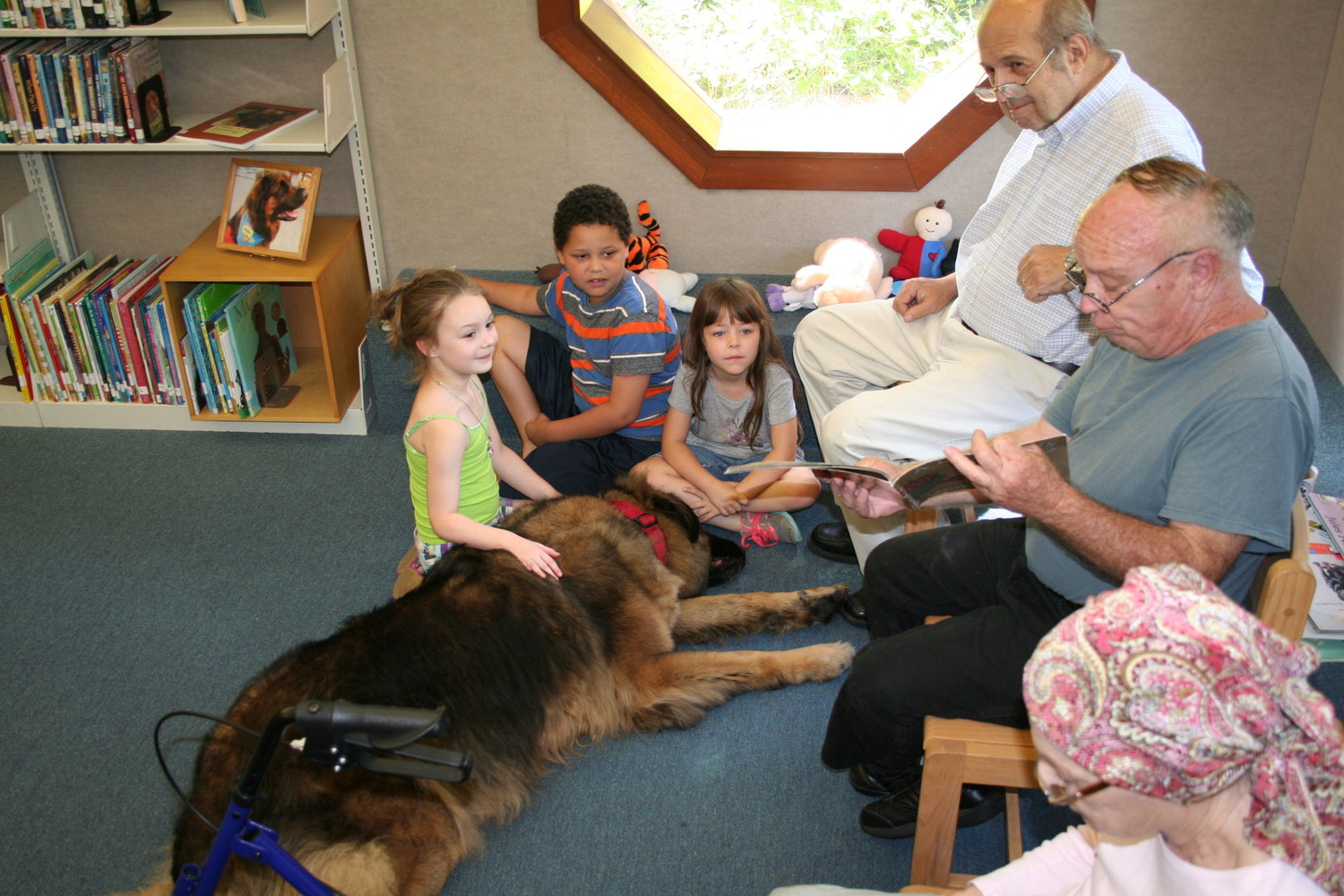 From left, Kelsi Baatz, 6, of Keystone Heights, Jordan Johntry, 7, Crista Johntry, 5, both of Melrose, snuggle with Clyde the Wonder Dog on Oct. 14 during Paws to Read at the Melrose Public Library. Also from left are Bill Morse, Library volunteer Mike Mason and Kathy Morse.