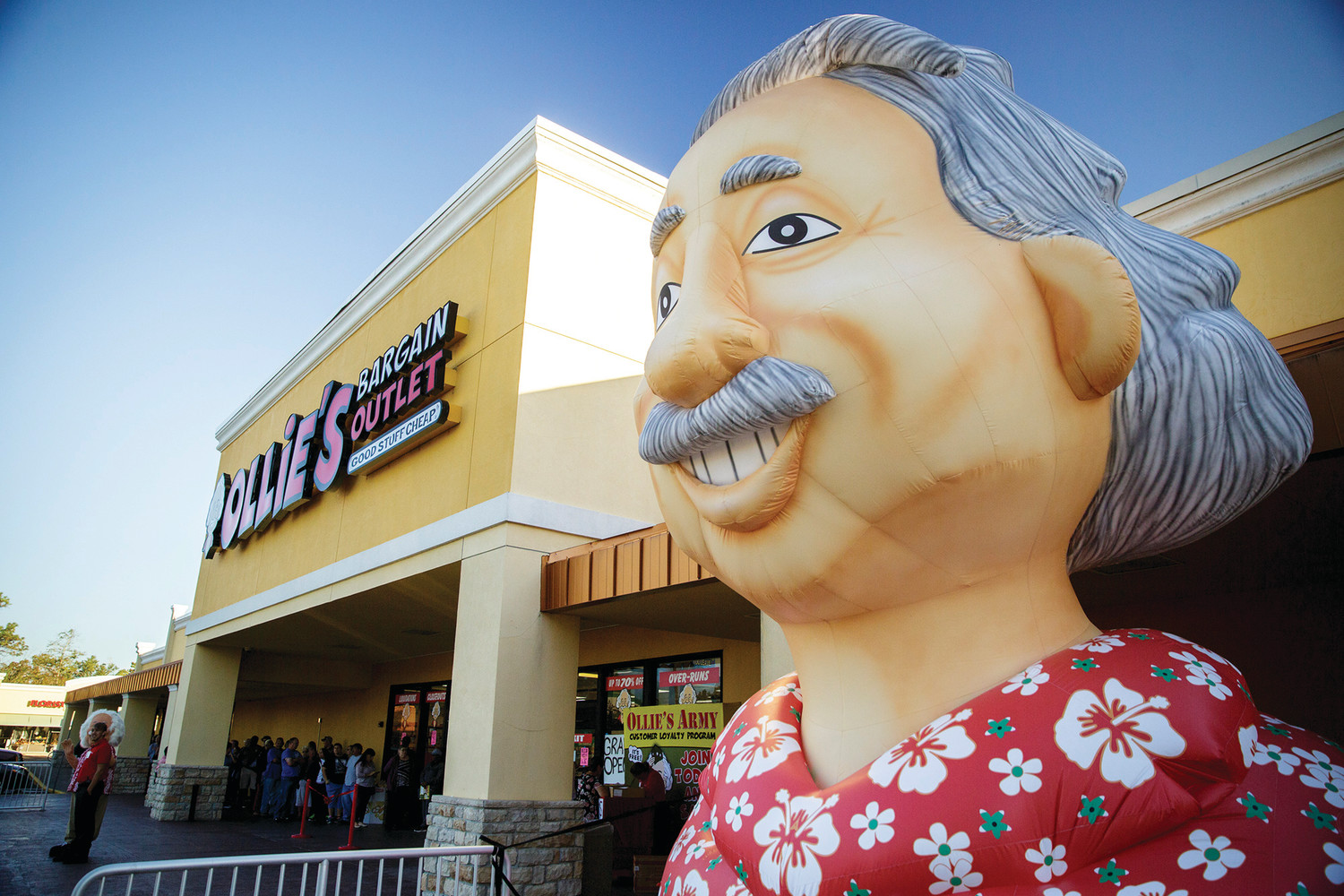 A large blowup Ollie bust sits outside the grand opening of Ollie's Bargain Outlet Wednesday morning on Blanding as customers wait to head inside the store.