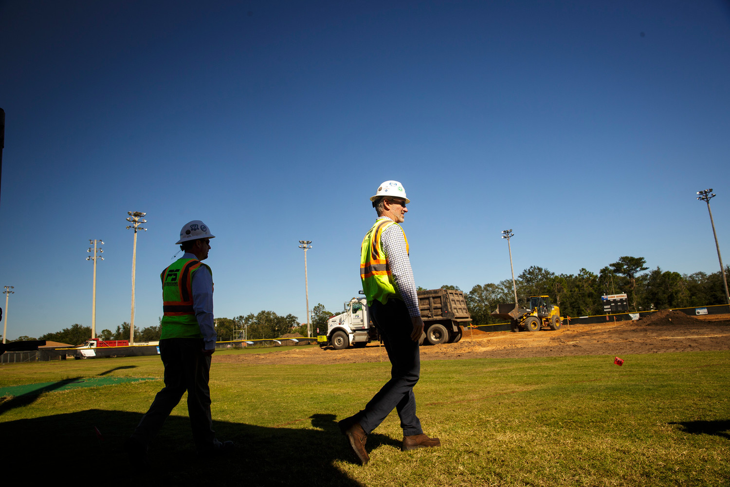 Orange Park High School graduate and Jacksonville-based contractor Ryan Schmitt walks onto the baseball field at OPHS where his company is providing free dirt work to help get the field back in top form.