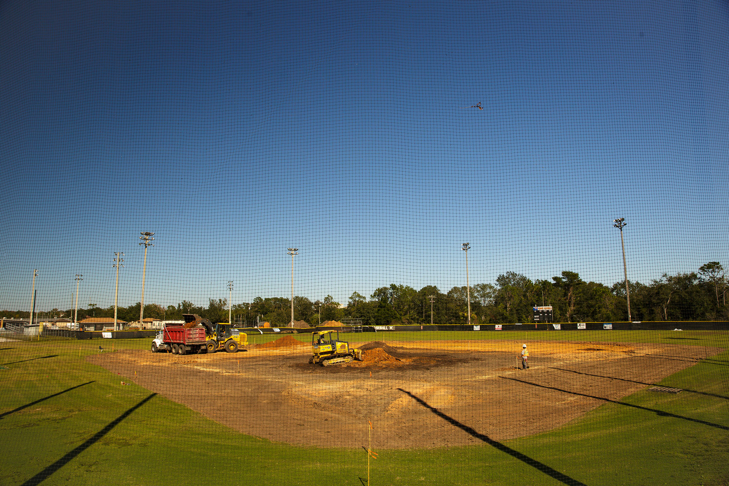 Dirt moving equipment from Petticoat-Schmitt levels out soil on the Orange Park High School baseball field Monday. The company's president, Ryan Schmitt, has donated his company's time and equipment to the project to help the school improve some drainage problems on the field.