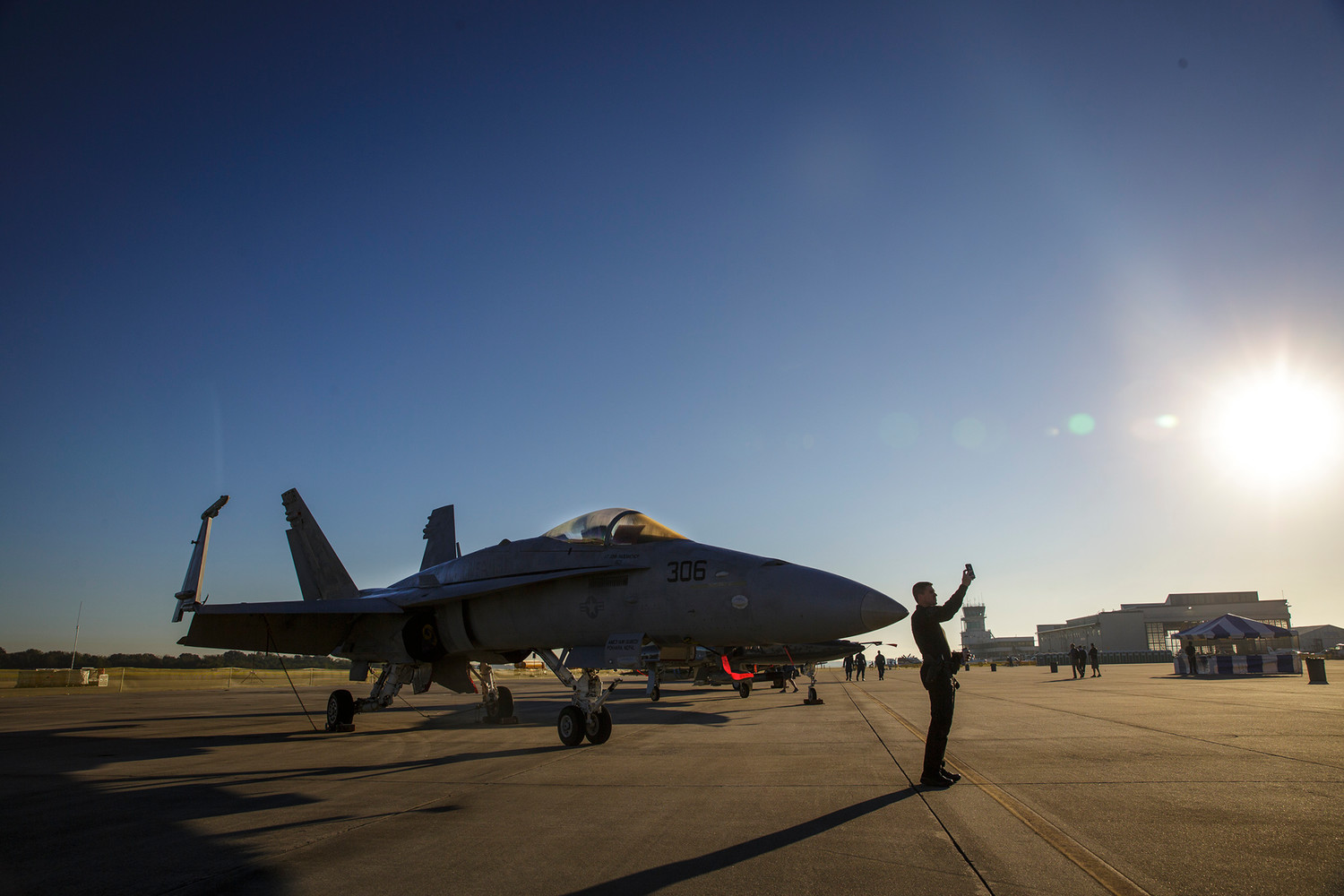 An FA-18 Super Hornet fighter jet sits on display at the Naval Air Station Jacksonville Air Show last week as an air show guest takes a selfie with the plane early Friday morning.