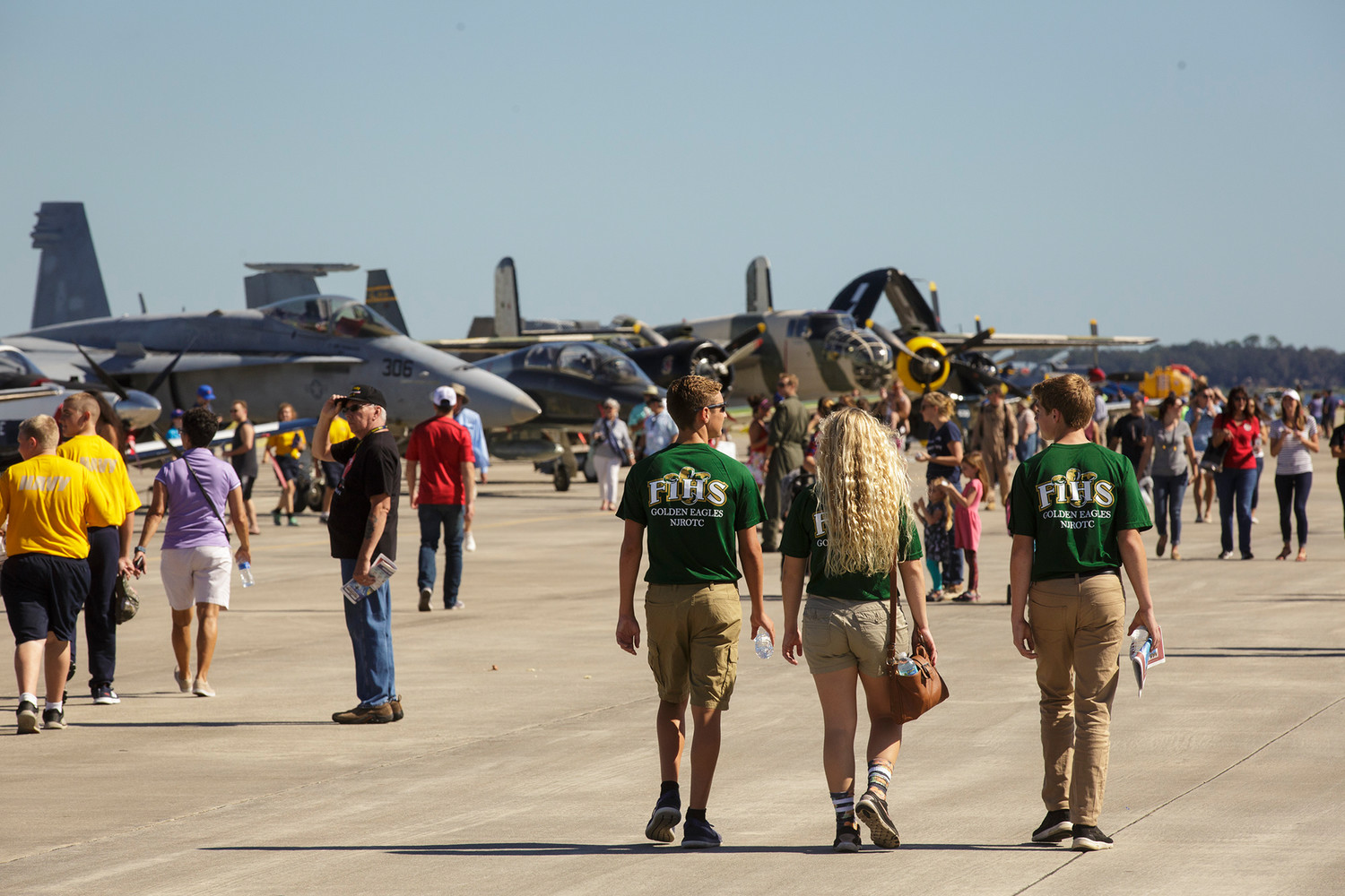 Members of the Fleming Island High School Navy JROTC program walk through a line of historic planes at Naval Air Station Jacksonville Friday during the rehearsal day for this year's air show.