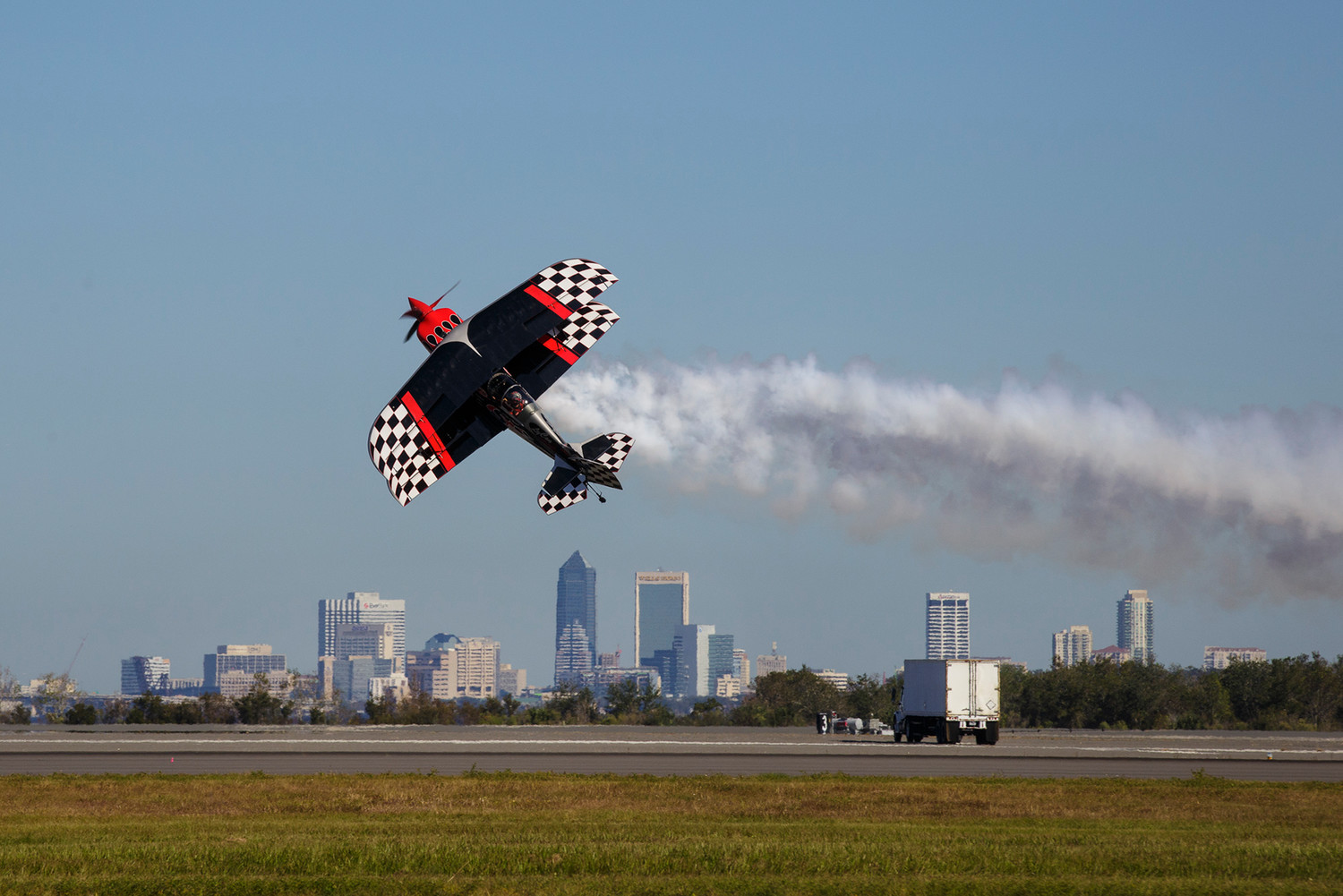 Stunt pilot Skip Stewart flies sideways across the image of Downtown Jacksonville on the runway at Naval Air Station Jacksonville while rehearsing his routine before the start of the base's air show.