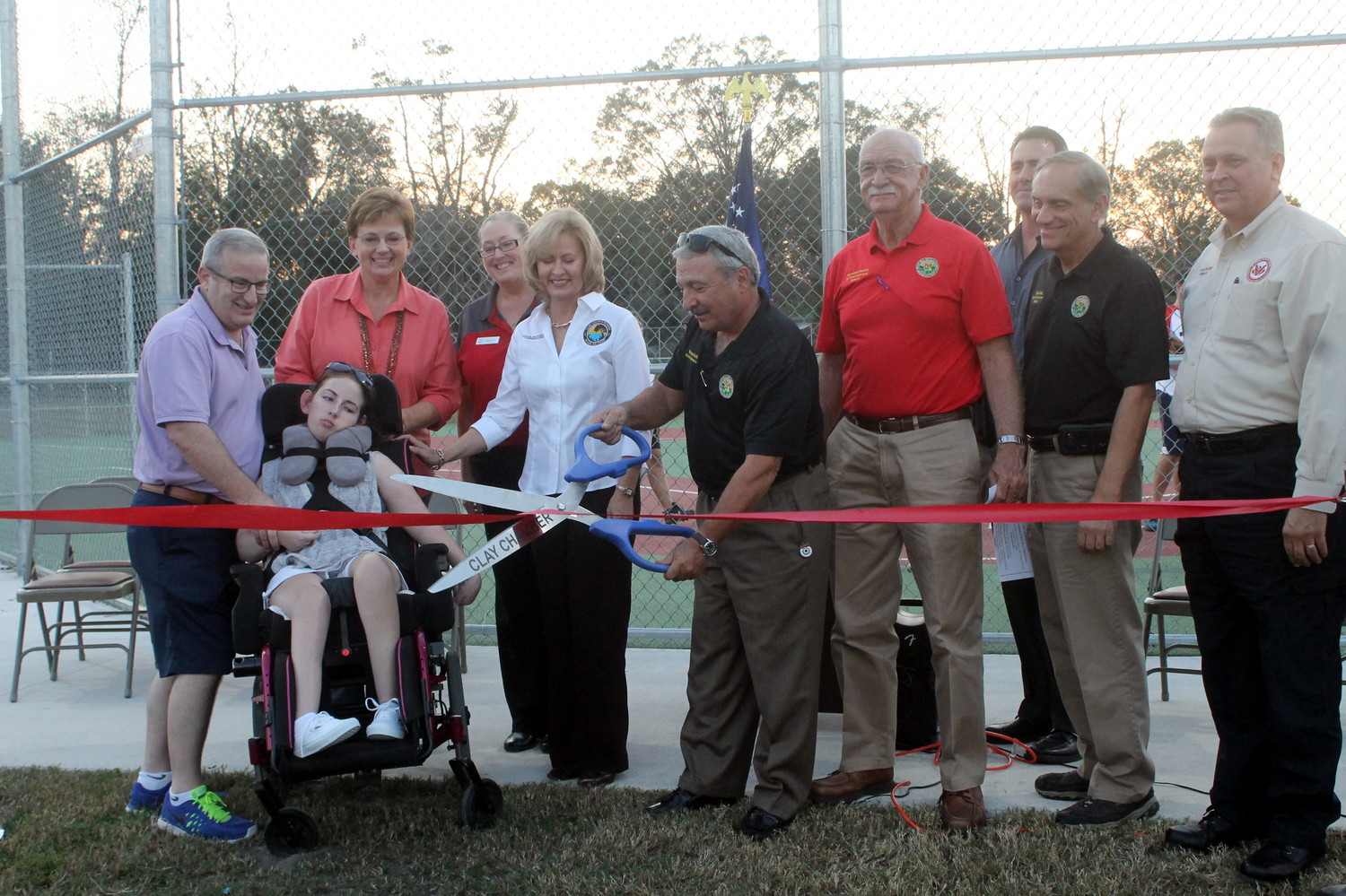 "Clay County Commissioner Wayne Bolla cuts ribbon to officially open the Moody Avenue Park baseball field while officials look on in the Nov. 7 ceremony. At right is former county commissioner Harold Rutledge who, in 2007, presented the idea for the ballpark to the commission in hopes of establishing a Miracle League team here. ""I was overwhelmed yesterday at the park; it was more than I could have ever imagined and hoped for the kids in our county who have special needs. It's going to be nice to go out there and see kids play together, regardless of their ability,"" Rutledge said. From left are Brian McElyea, Brienna McElyea, Jill McElyea, Ronna Smith, Diane Hutchings, Bolla, County Commissioner Gayward Hendry, James Holdhouse and County Commissioner Mike Cella."