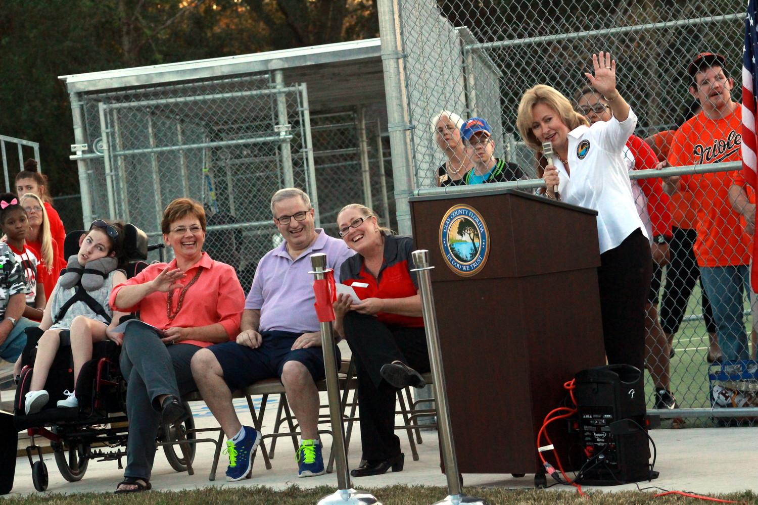 Clay County Commission Vice Chair Diane Hutchings waves to spectators of the ribbon cutting ceremony for the new Moody Avenue Park baseball field while, from left, Brienna McElyea, Jill McElyea, Brian McElyea and Ronna Smith smile.