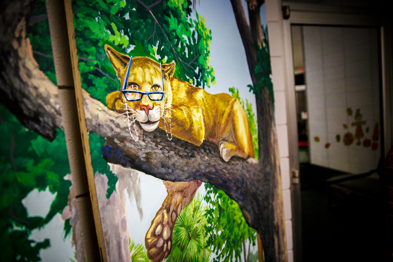 A vision-impaired Florida panther sits lazily on a branch on a mural painted by Jacksonville artist Anthony Rooney for the Green Cove Springs Library.