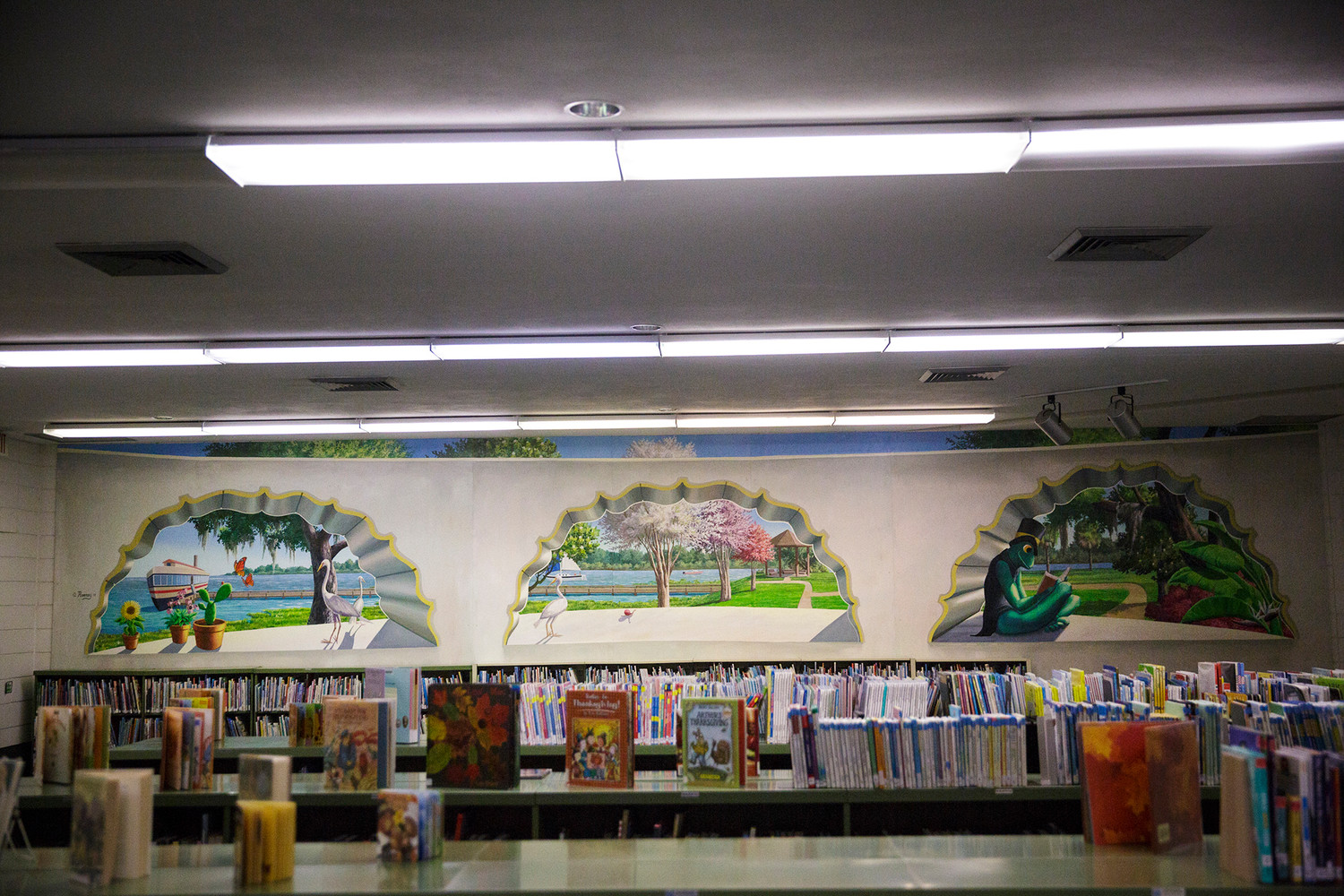 Anthony Rooney's first mural sits in the Green Cove Springs Library's children's section. Rooney returned to the library Wednesday morning to install part of the second phase of the mural project.