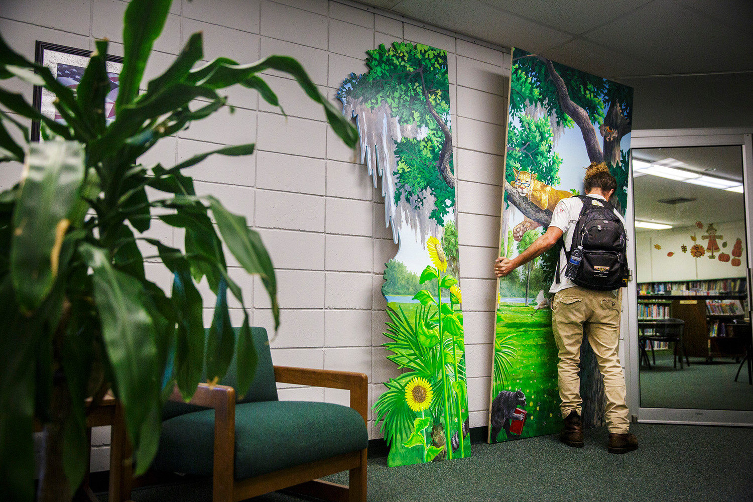 Jacksonville artist Anthony Rooney holds a panel in place while figuring out where to position them on the walls just outside the children's section at the Green Cove Springs Library on Wednesday morning.