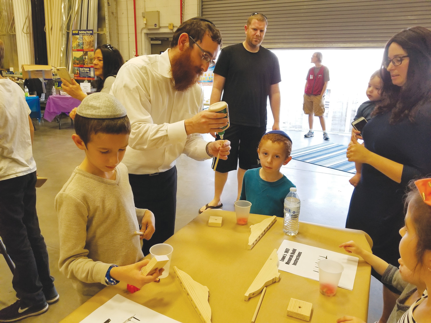 Rabbi Shmuly Feldman, second from left, assists children with making menorahs in preparation for the annual celebration of Hanukkah at a workshop held Dec. 2 at Lowe's on Kingsley Avenue.