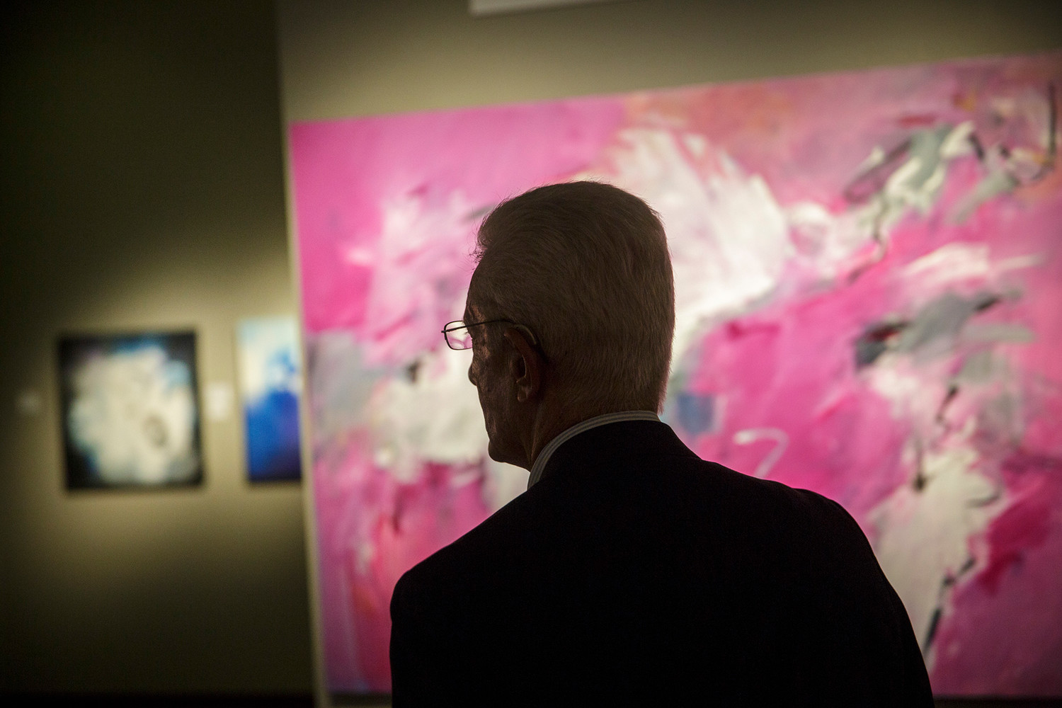 "A man walks through the ""In the Spirit"" exhibition by Orange Park artist Jeanne Pellegrino that is currently on display at the Thrasher Horne Center."