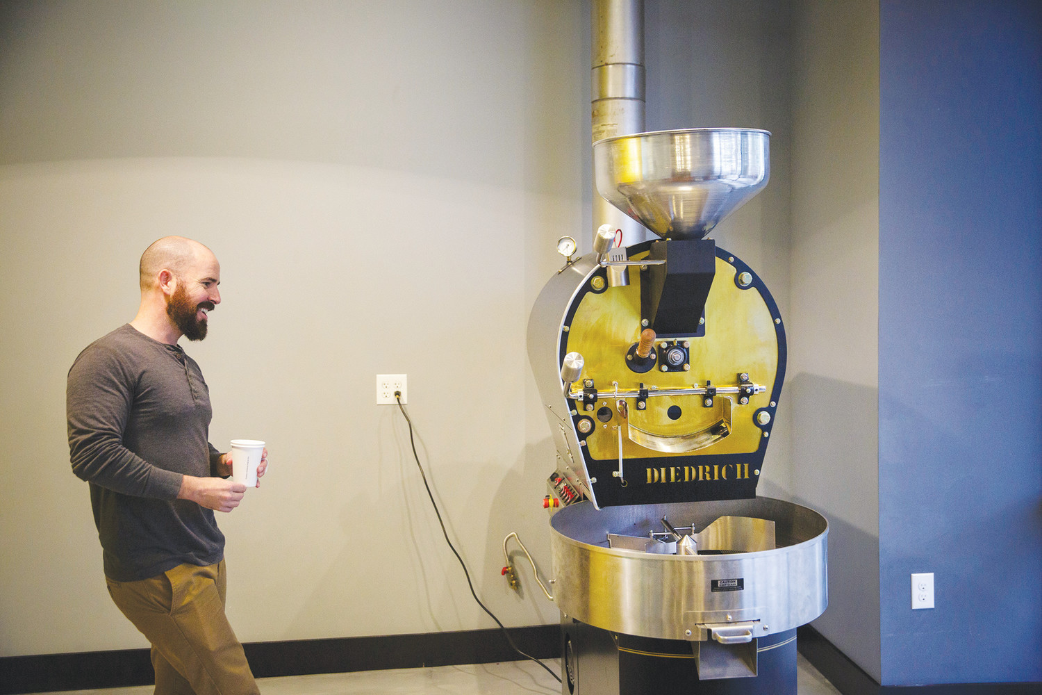 Owner Steven Kelley stands in the new Brass Tacks Coffe Co. storefront in Green Cove Springs next to the company's new custom coffee roaster.