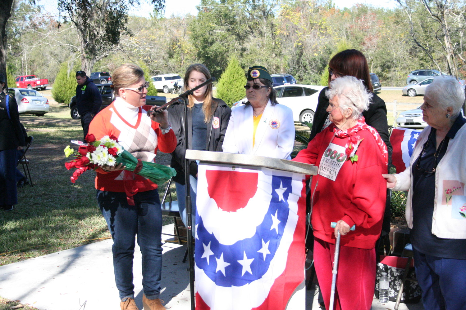 Mary Justino of Lake Asbury presented Joan Jones, 90, of Keystone Heights, a bouquet of roses and assorted flowers as a community thank gift for her 12 years of honoring veterans and coordinating different veterans' events at the Keystone Heights City Cemetery. Jones, a native of Australia, came to the U.S. at age 19 after meeting her husband during World War II.
