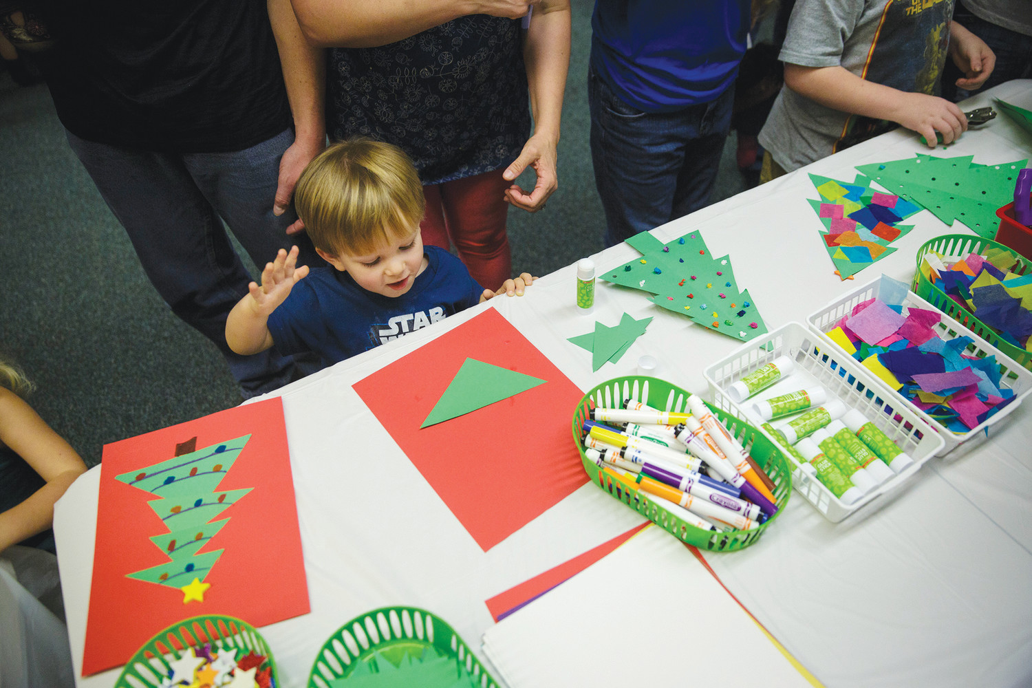 Two-year-old Middleburg resident Jason Marshall creates his own version of a Christmas tree Monday at the Green Cove Springs Library during a visit from Santa.