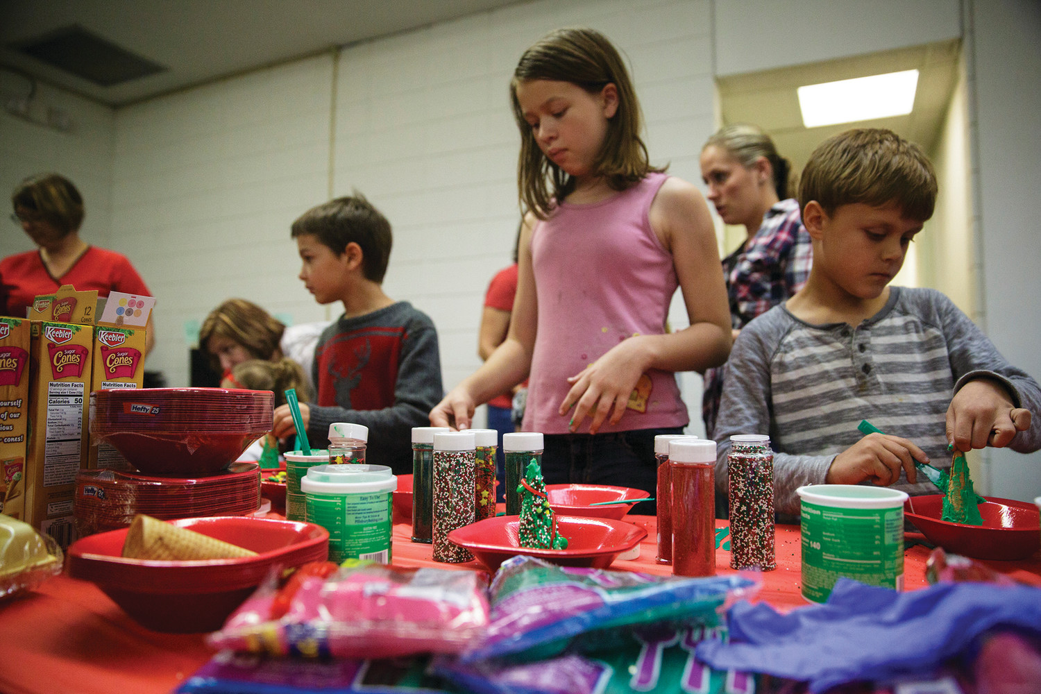 Children create icing and candy christmas trees using upside down ice cream cones as the base for the tree shape Monday evening at the Green Cove Springs Library.