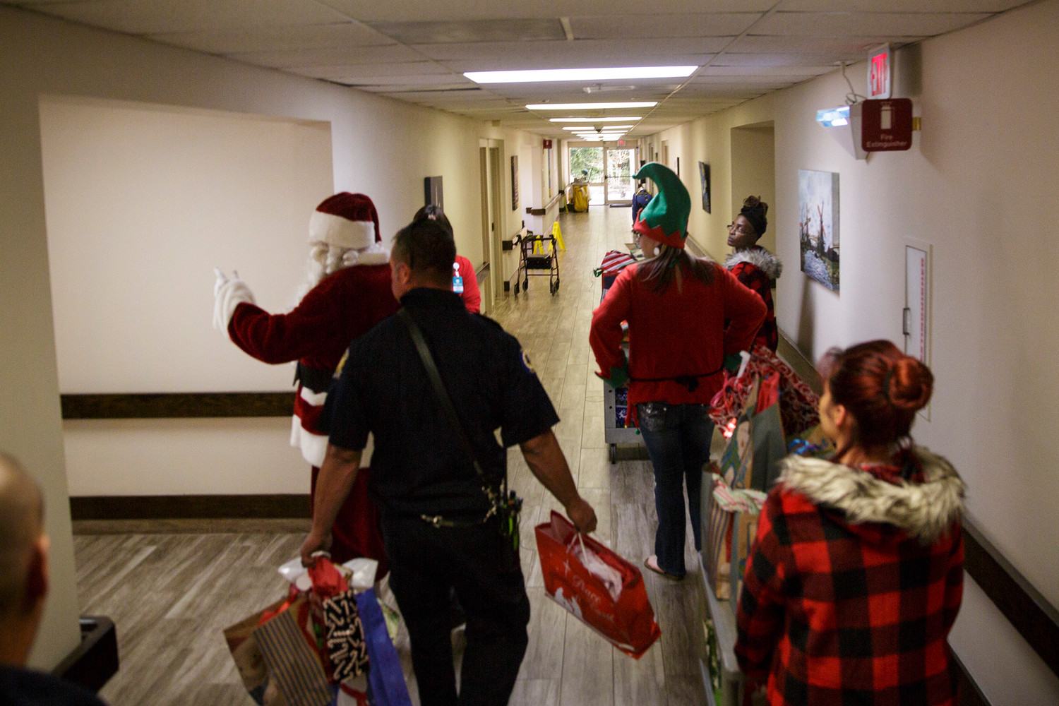 Members of Orange Park's fire and police forces make their way down the hall at Oak View Rehabilitation Center Thursday while carrying out gift deliveries for the annual Home Instead effort to put Christmas gifts into the hands of Clay County's elderly population.