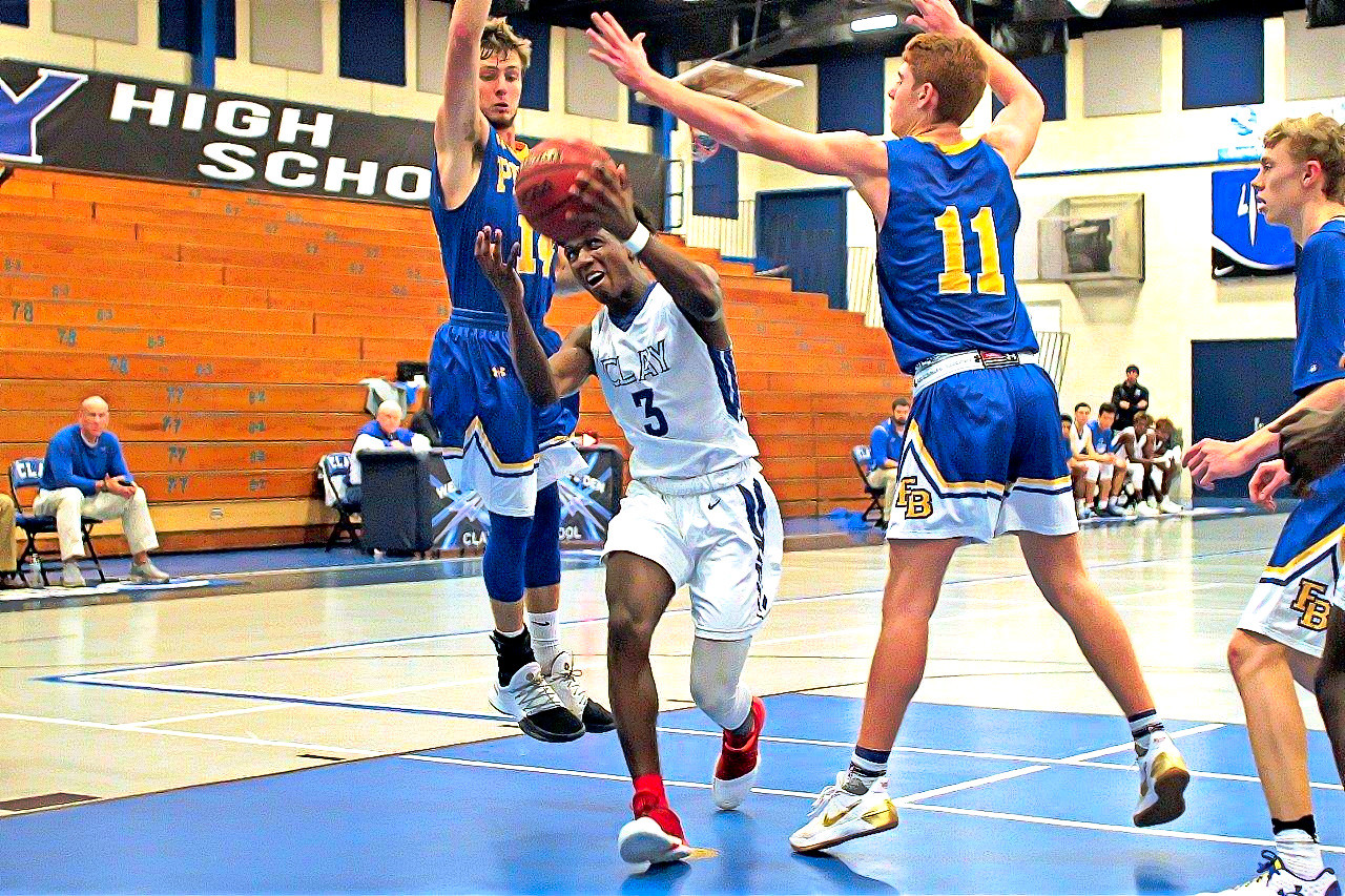 Clay High guard Kijan Boone slices through two defenders from Fernandina Beach in Clay Christmas Tournament win Thursday afternoon.