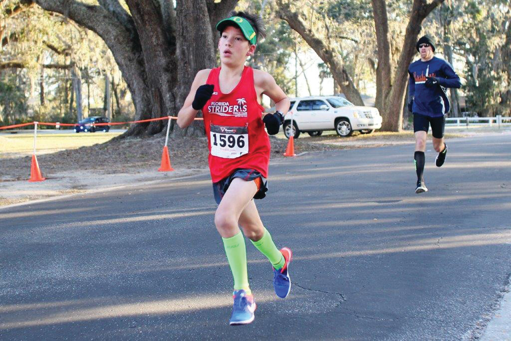 John Keester, 11, powers to finish for first place in age group in 19:10 and 14th overall.