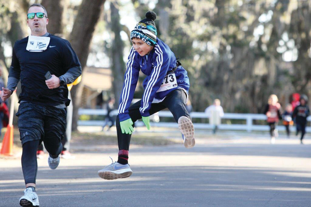 Ten year old Nick Santana jumps for joy at finish in 32:41 at Resolution Run 5K.