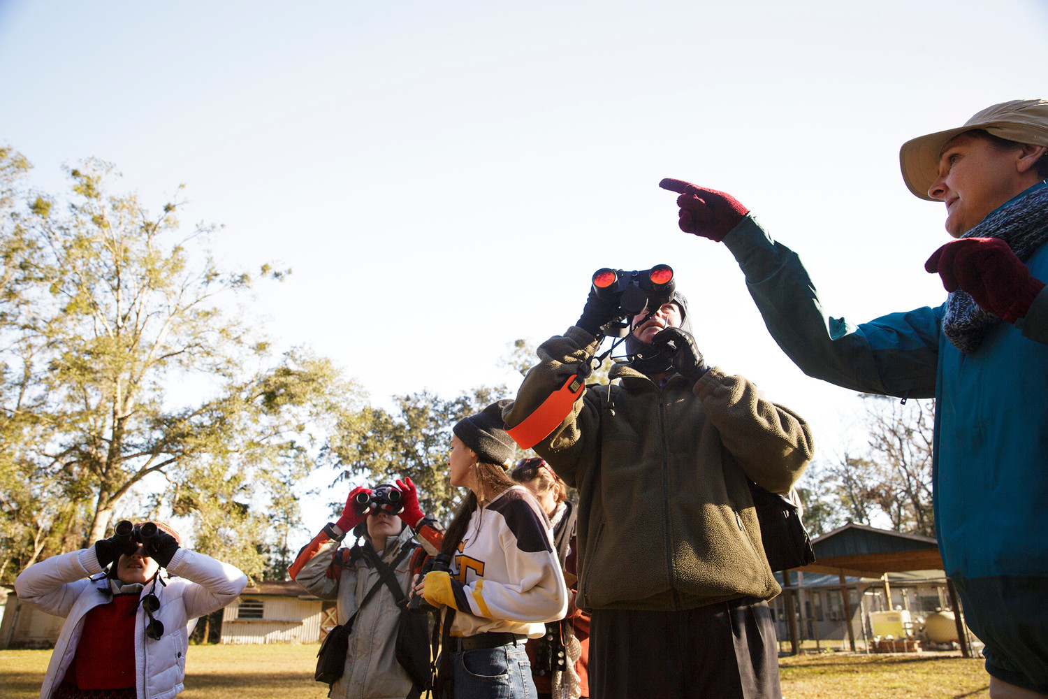 Participants in the annual Christmas Bird Count for Kids direct their binoculars to a tree where a bird had been spotted by the experienced birders who led groups throughout the grounds at Camp Chowenwaw to check birds off their list and make their count.