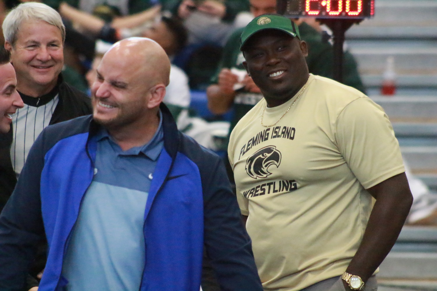 Fleming Island wrestling coach P.J. Cobbert, right, smiles in pre-championship match moment with long-time South Dade coach Victor Balmeceda, who has 12 state titles in his pocket.