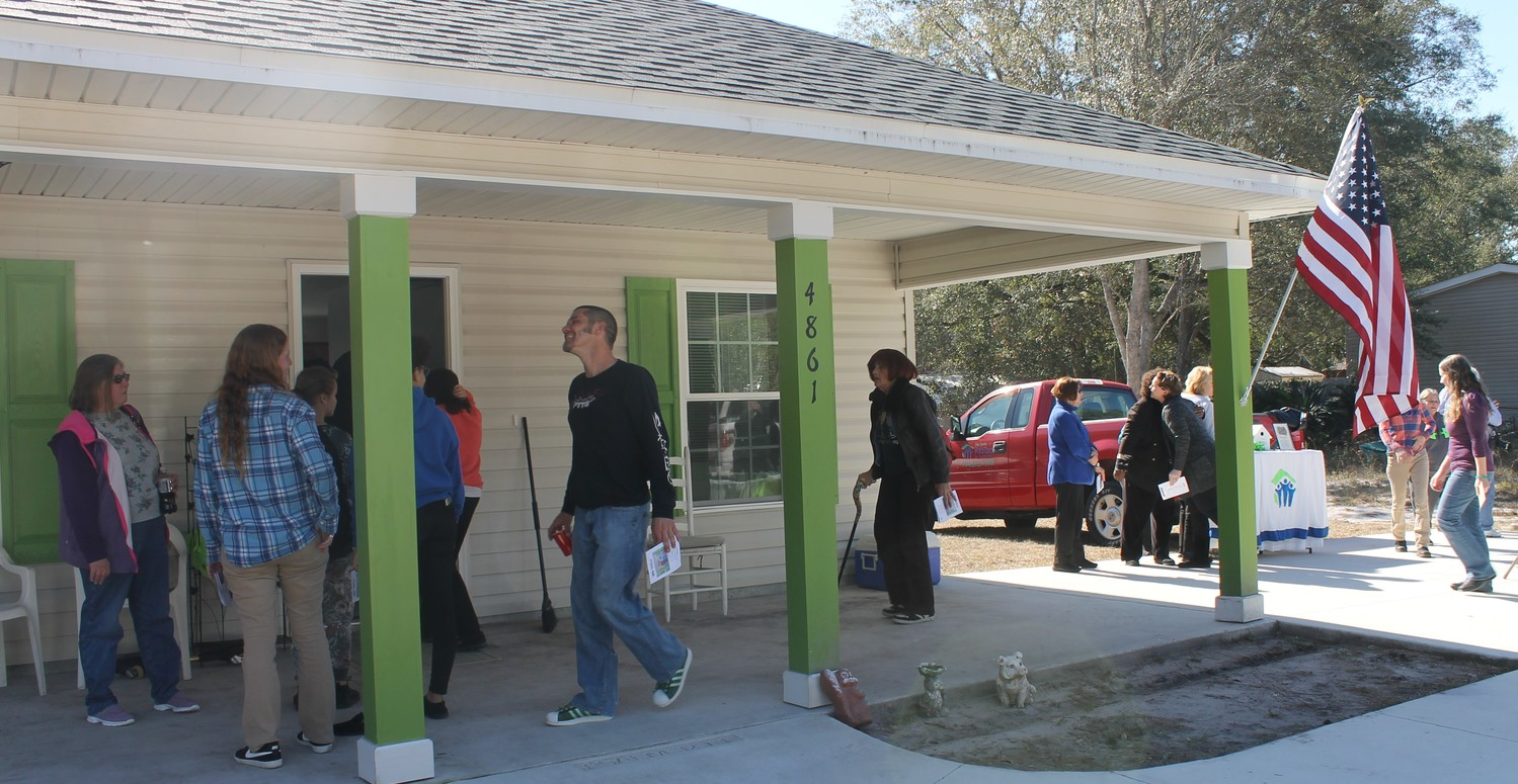 Family, friends and supporters and staff of Clay County Habitat for Humanity tour Stephanie Mabey's new home Jan. 19 during a dedication ceremony. Mabey logged almost 300 hours in helping build the home.